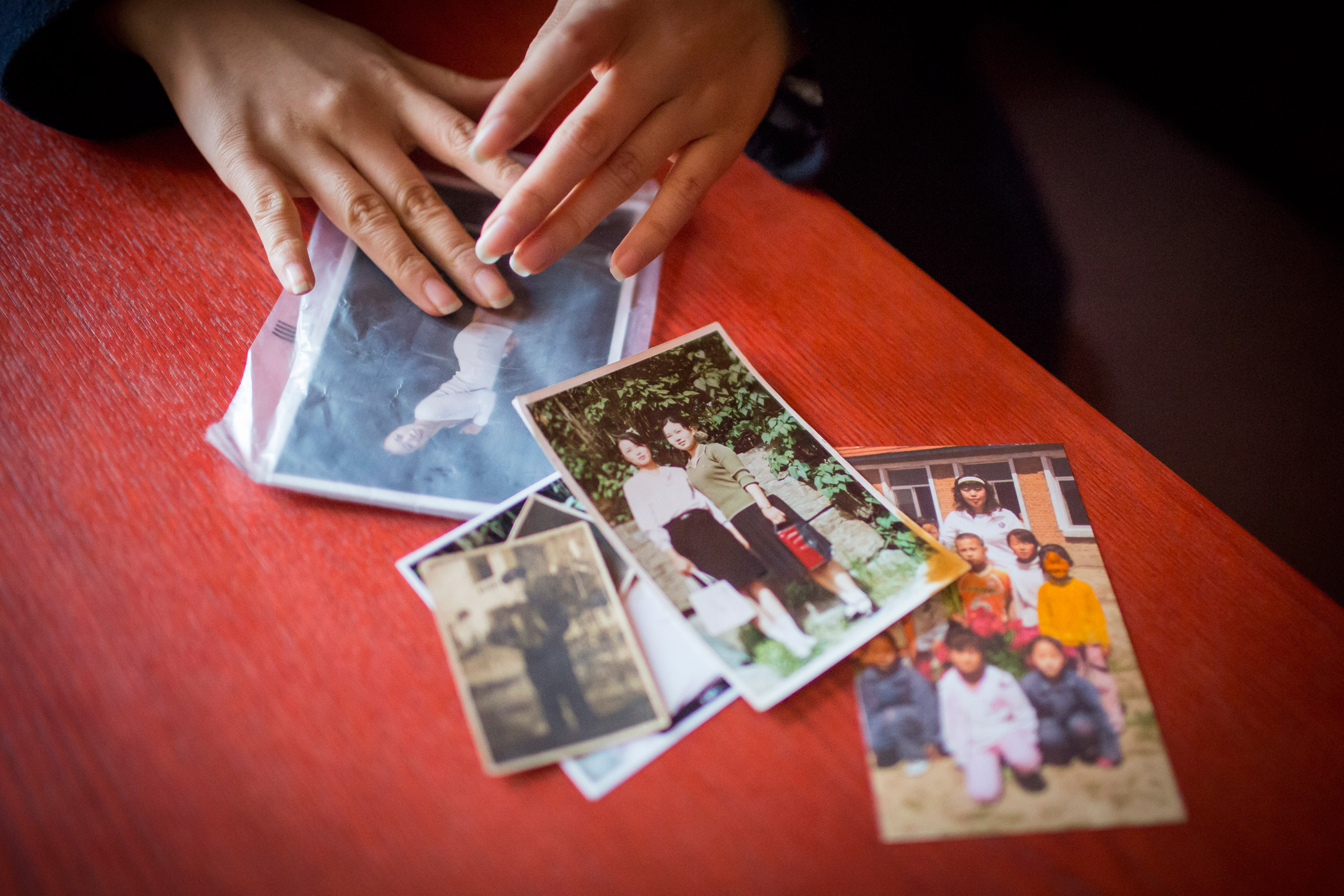 Kyoung-ok shows photographs on Feb. 1, 2015, that she brought with her on the 10-month journey from North Korea through China, Vietnam and Cambodia to South Korea. Other than a backpack full of food and a few clothes, these pictures were all that she and her mother brought with them when they left.
