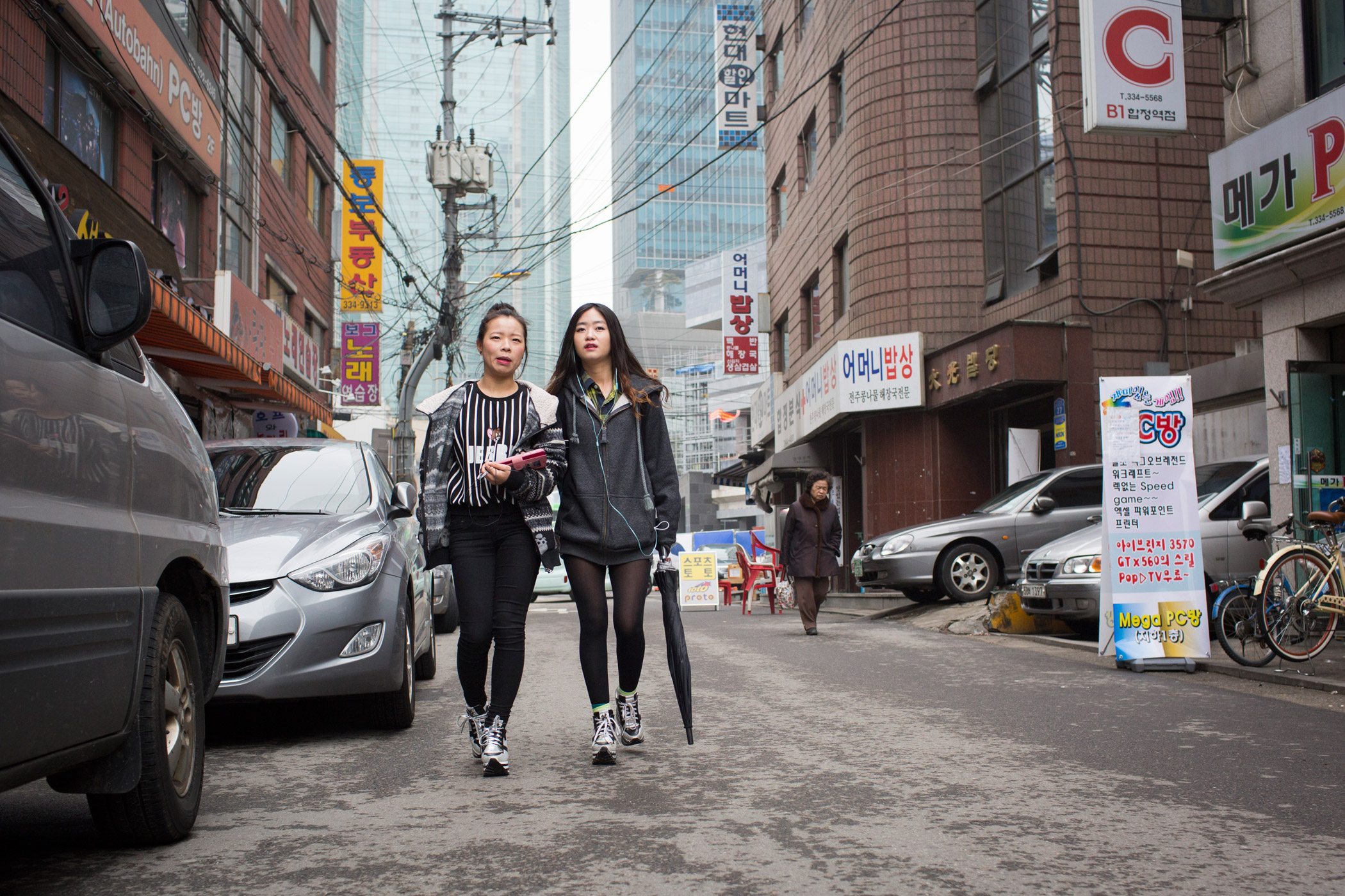 Donning matching shoes, North Korean refugees Kim Kyoung-ok,  and Sarah walk arm-in-arm on their way to a Christian church service on Feb. 21, 2015 near Hapjeong, Seoul, South Korea. The women met shortly after they each arrived separately in South Korea at a resettlement camp for refugees.