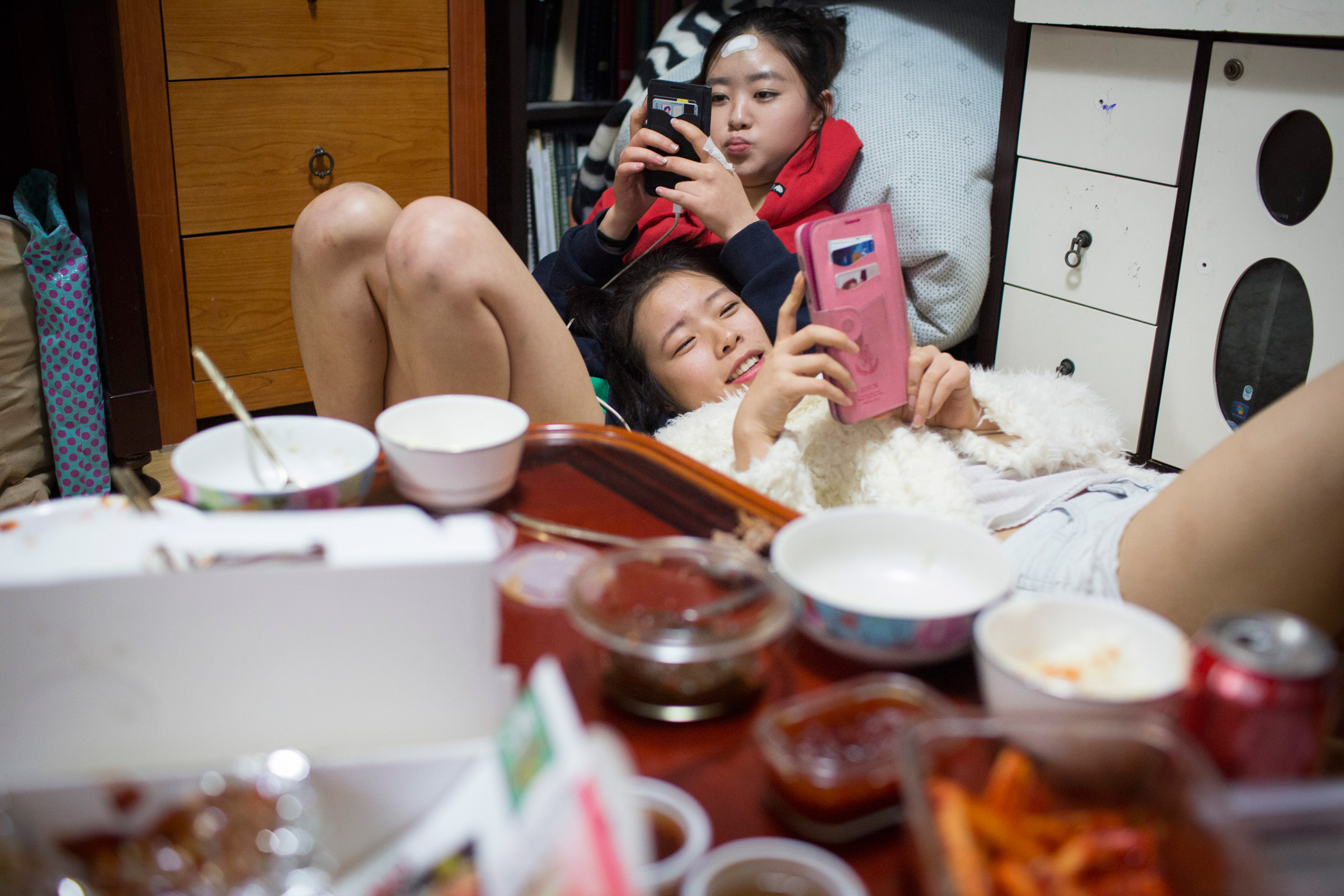 Kyoung-ok and Sarah spend time on their phones after sharing takeout for dinner at Kyoung-ok's apartment on Feb. 28, 2015 in Mia, Seoul, South Korea.