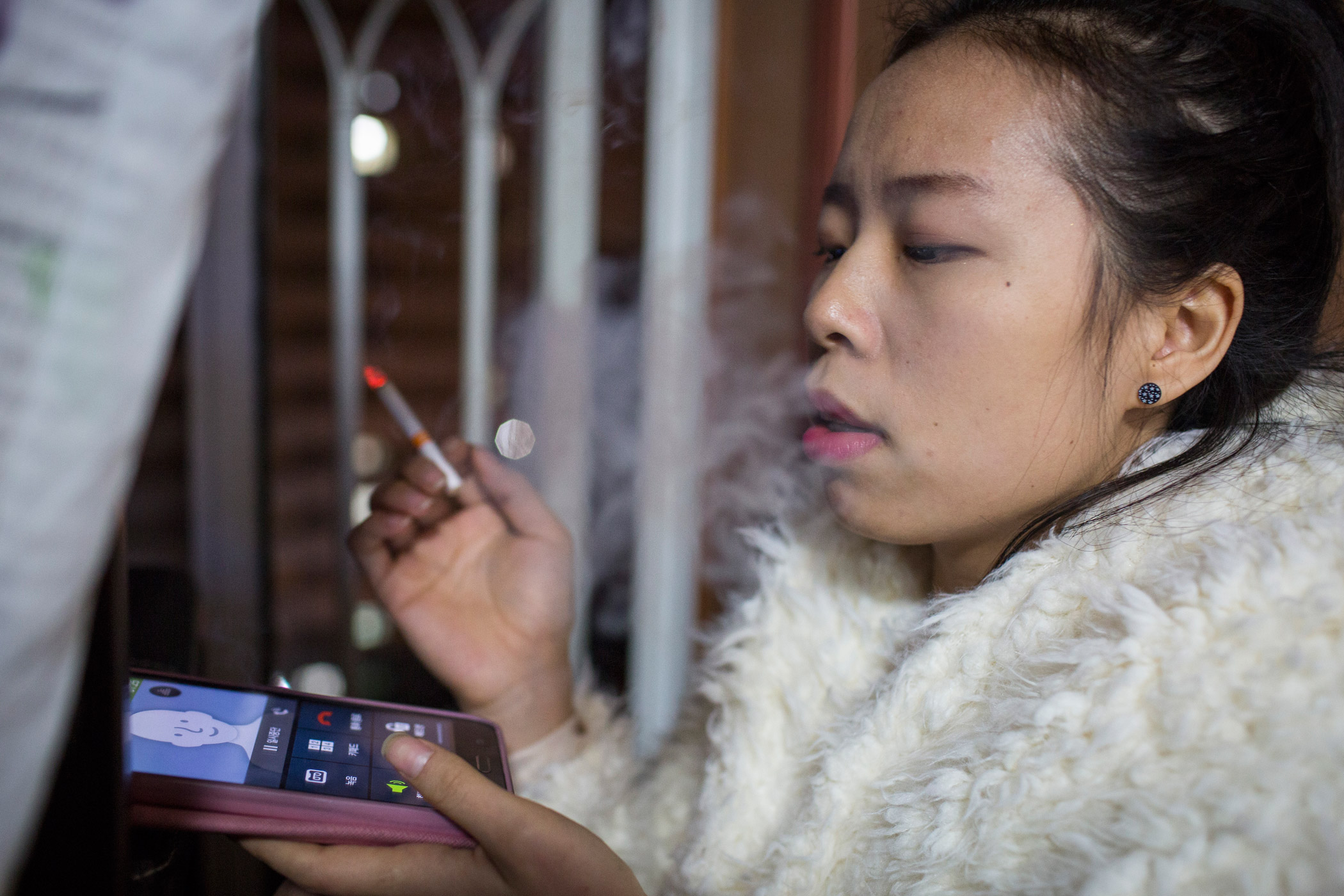 Kyoung-ok smokes on her balcony on Feb. 28, 2015 in Mia, Seoul, South Korea.