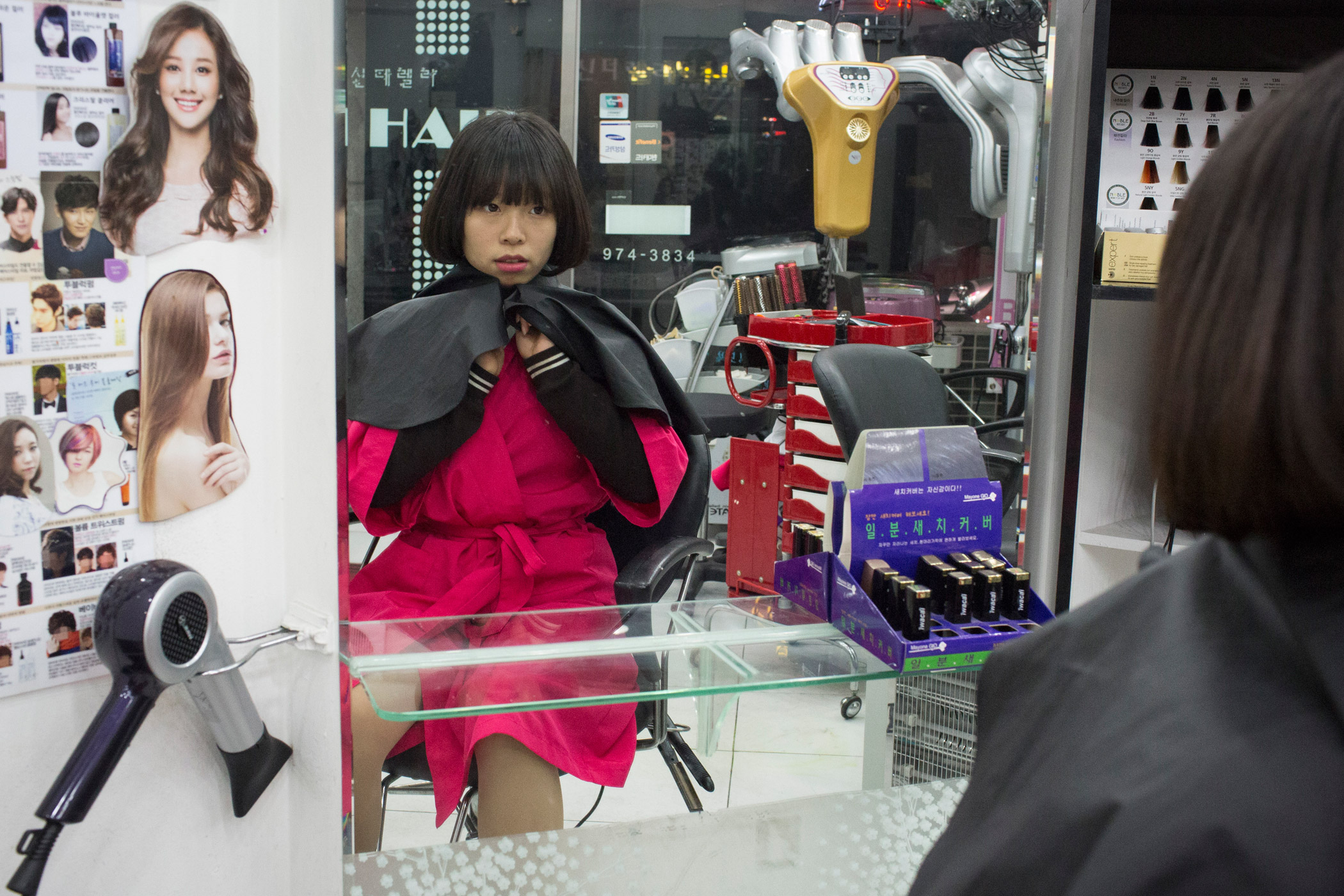 Kyoung-ok looks receives a haircut and style in her aunt's salon in Seoul, South Korea. She is training to be a hair and nail designer and helps her aunt out when she can. In North Korea, there is little room for self-expression in hair styles, where acceptable styles are sanctioned.