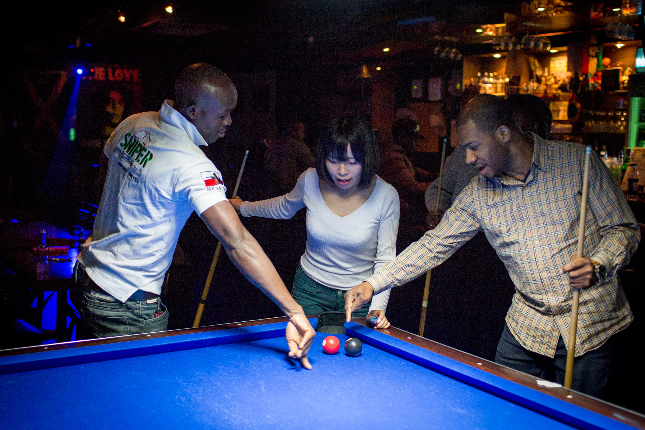Kyoung-ok plays pool with Christian King of Liberia, left, and Jerry Alexander of Canada, right, at Club Zion, a Jamaican bar, on March 19 in Itaewon, Seoul, South Korea. Kyoung-ok loves to visit Itaewon, which is a foreigner-heavy neighborhood, to meet people from different places and sample foreign food.