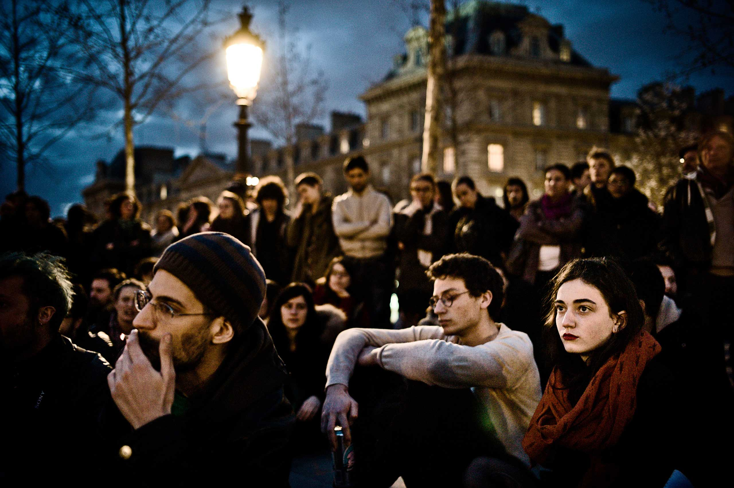 The crowd sits in circles listening to members of the movement speak,  all evening, every day at the Nuit Debout.