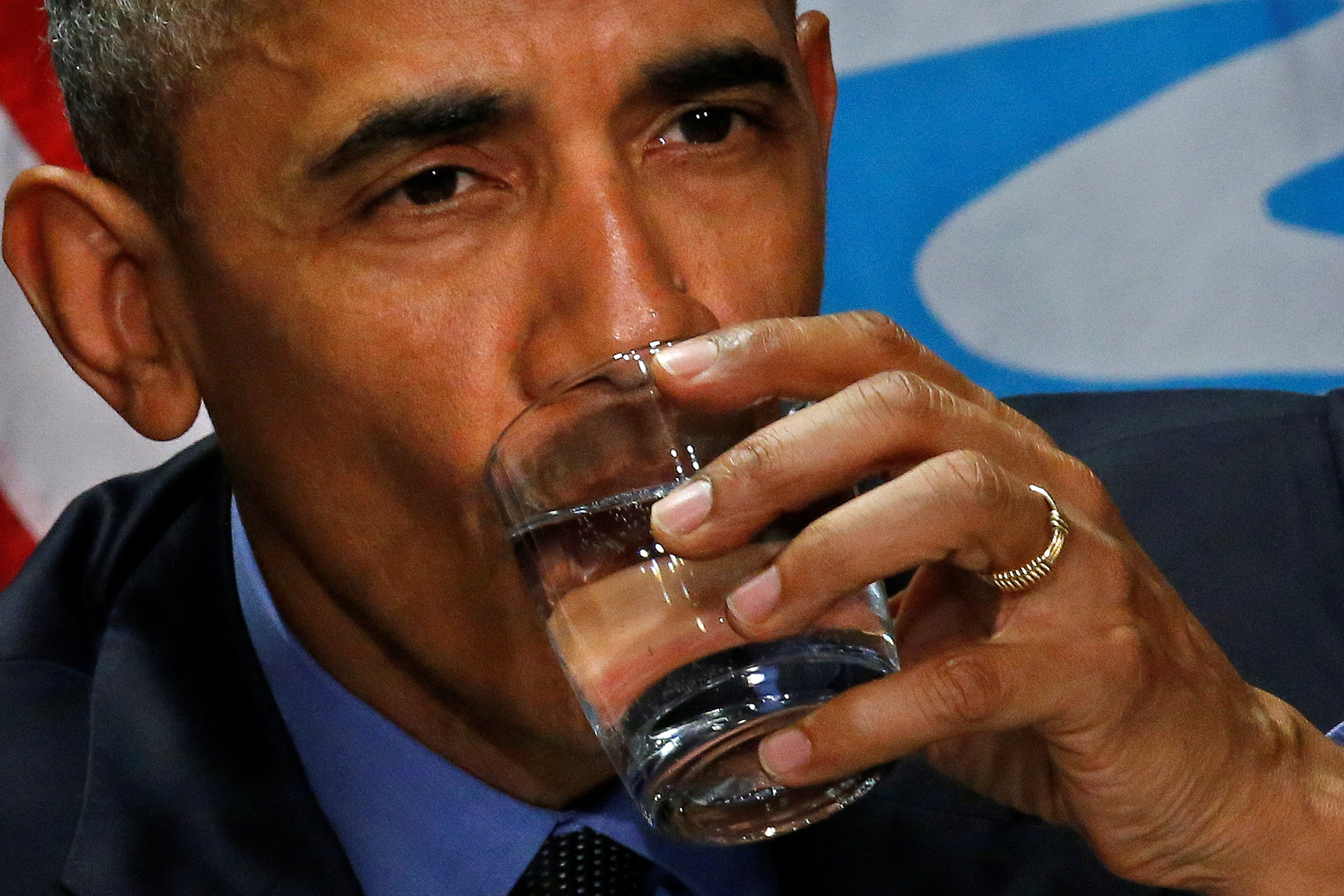 President Obama drinks a glass of filtered water from Flint during a meeting will local and federal authorities in Michigan, on May 4, 2016