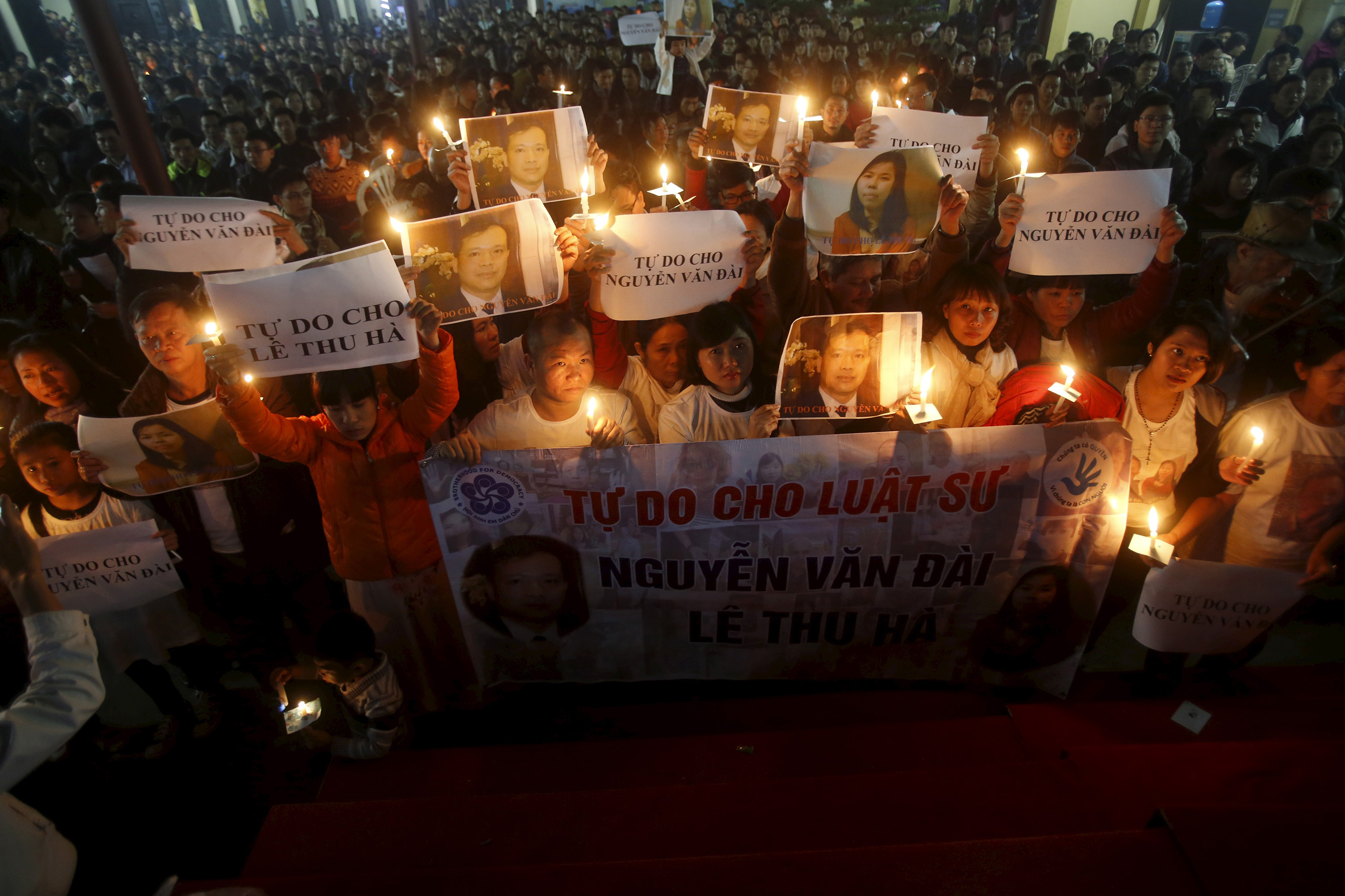 Vu Minh Khanh holds an image of her husband Nguyen Van Dai as Catholics hold candles and image of Dai's assistant Le Thu Ha during a mass prayer for Dai and Ha at Thai Ha church in Hanoi, Dec. 27, 2015.