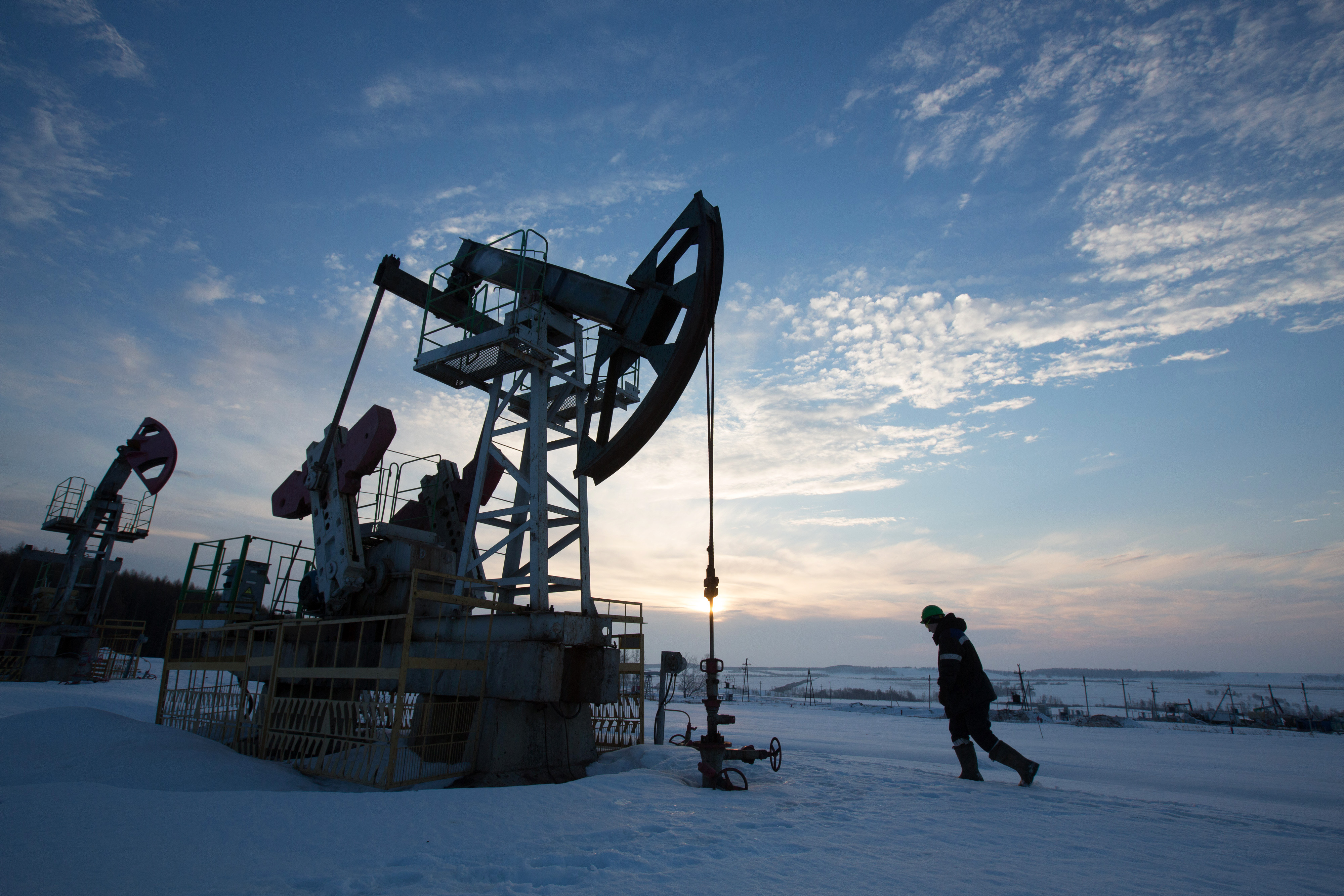 An oil worker inspects a pumping jack, also known as a 'nodding donkey,' during drilling operations in an oilfield operated by Bashneft PAO in the village of Otrada, 150kms from Ufa, Russia, on Saturday, March 5, 2016.
