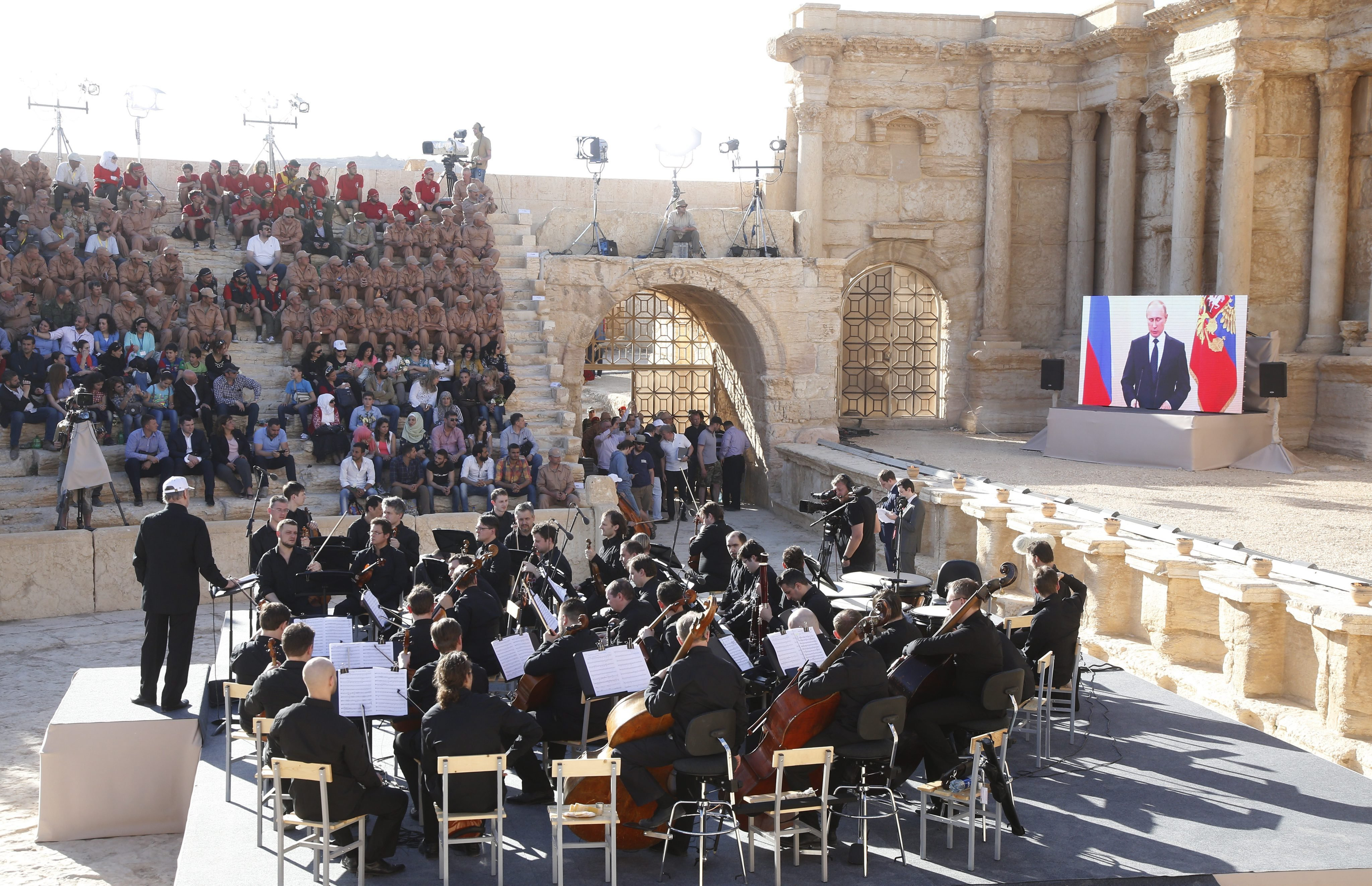 Russian President Vladimir Putin, via a live video feed (screen at right), delivers a speech during a concert by the Mariinsky Theater Orchestra in Palmyra amphitheater in Syria, on May 5, 2016.