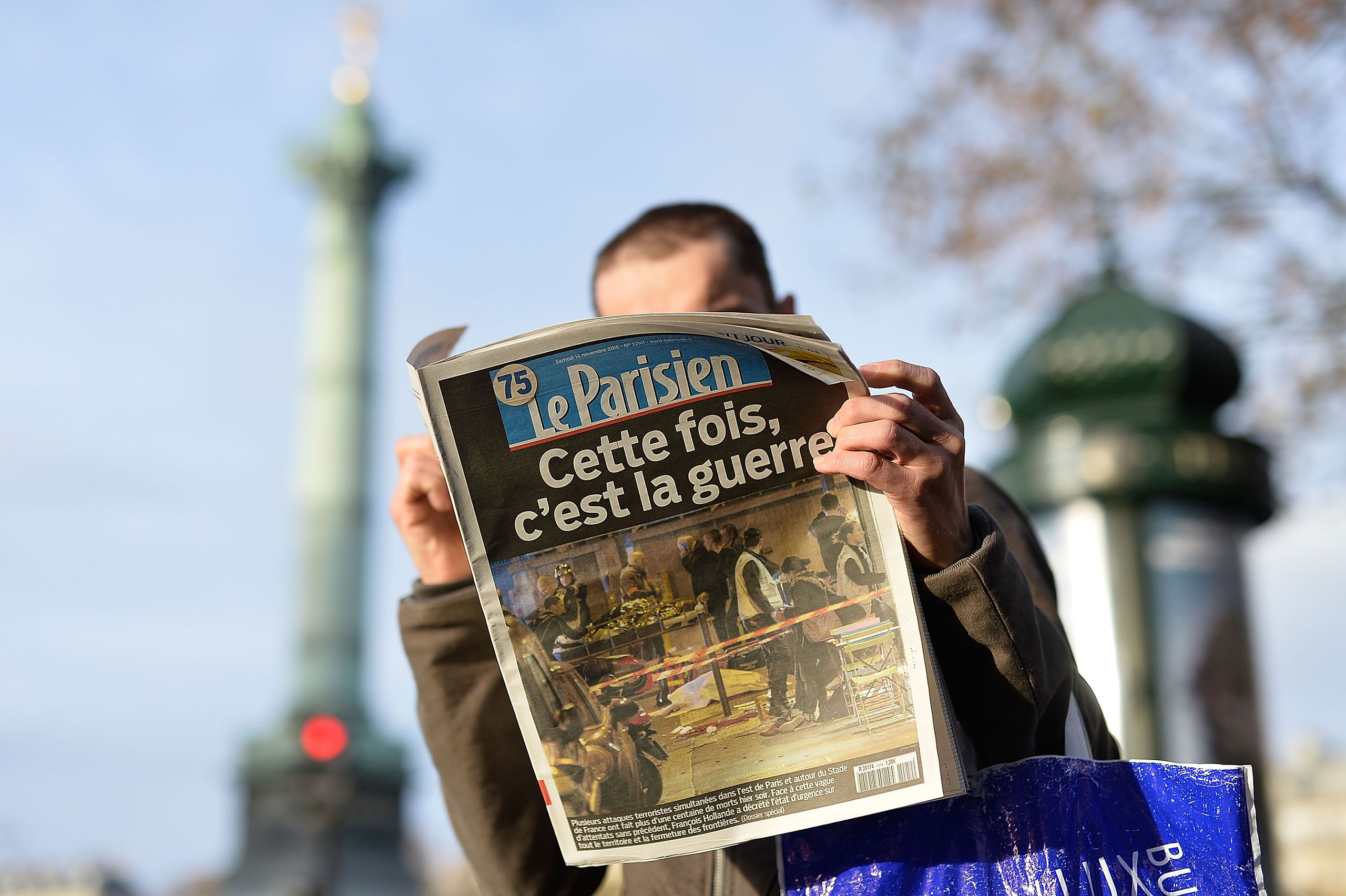 A man reads a French newspaper after a terrorist attack in Paris on Nov. 14, 2015.