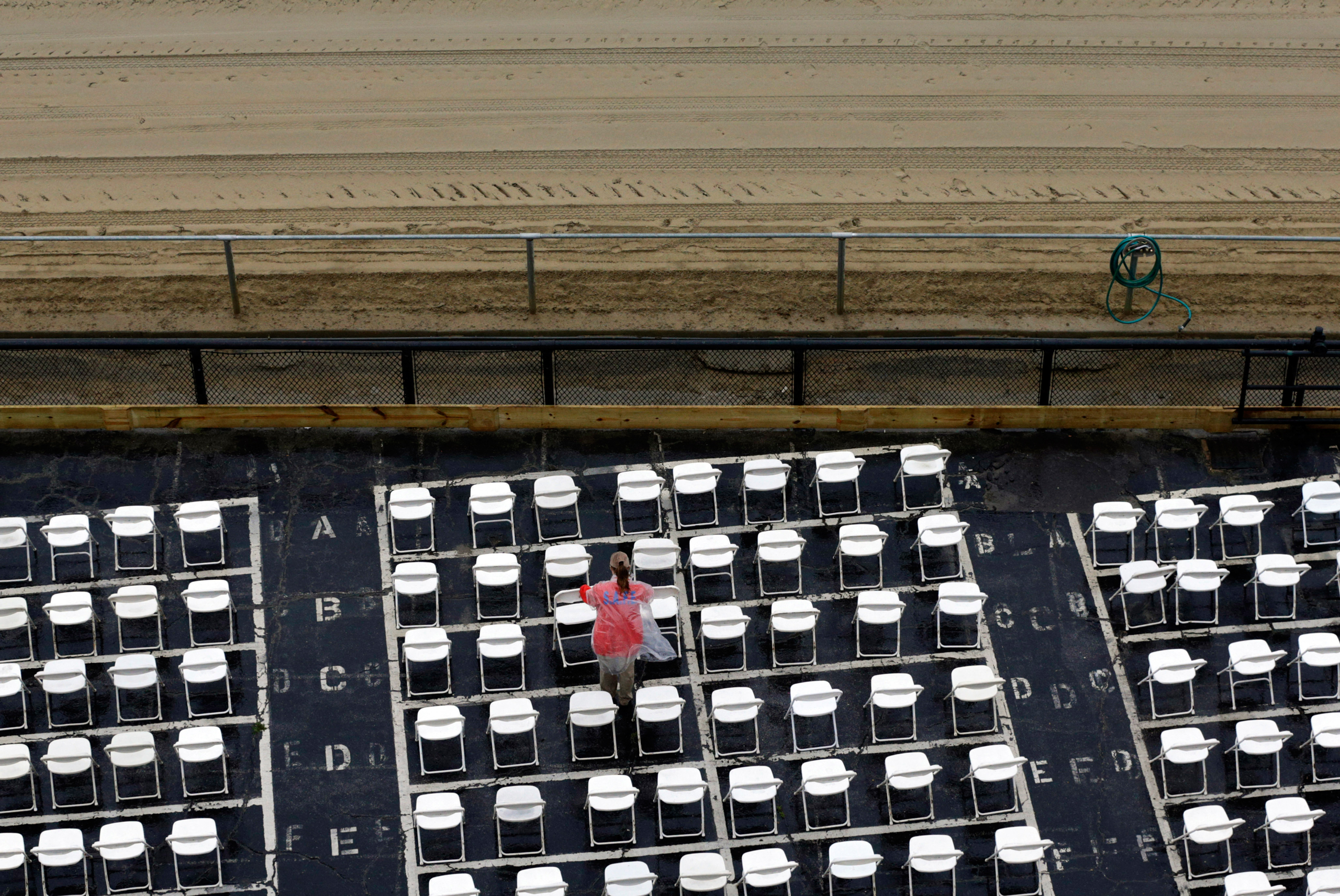 An usher clears water off of trackside seats as rain falls before the 141st Preakness Stakes horse race at Pimlico Race Course in Baltimore, Md., on May 21, 2016.