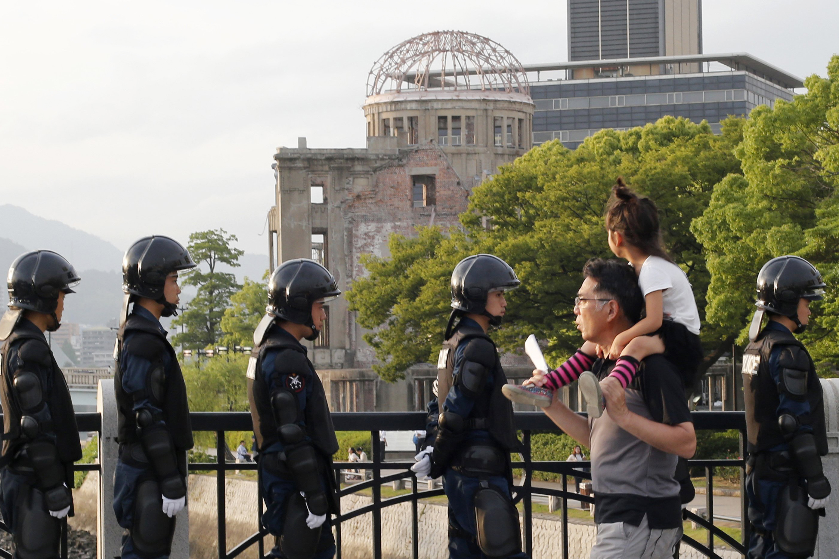 With the Atomic Bomb Dome as a backdrop, passers-by move past riot police near Hiroshima Peace Memorial Museum in Hiroshima, southwestern Japan, Thursday, May 26, 2016.