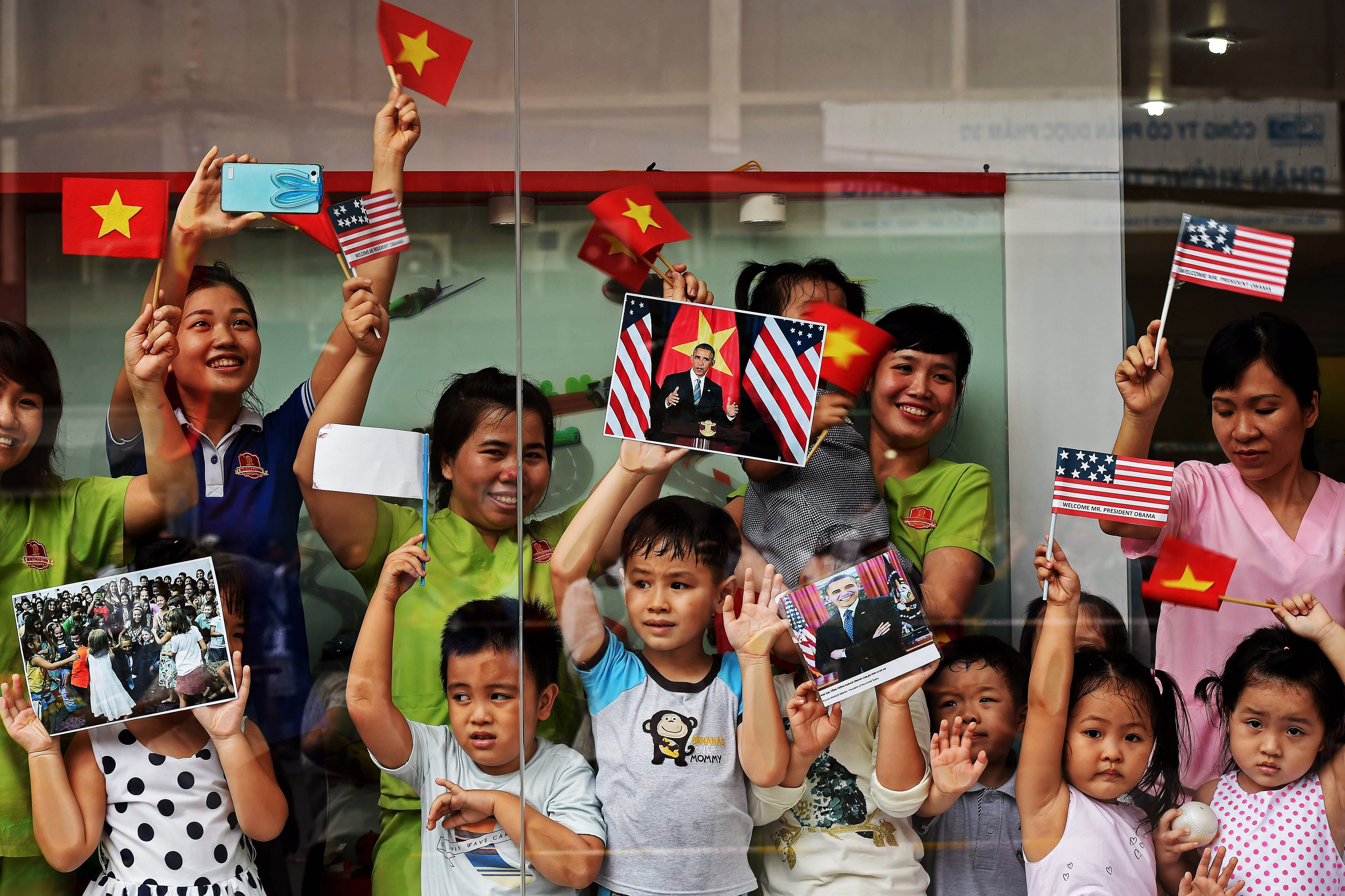Women and children  line the streets to catch a glimpse of President Barack Obama on his way to the airport at the end of two-day visit to Ho Chi Minh City on May 25, 2016.