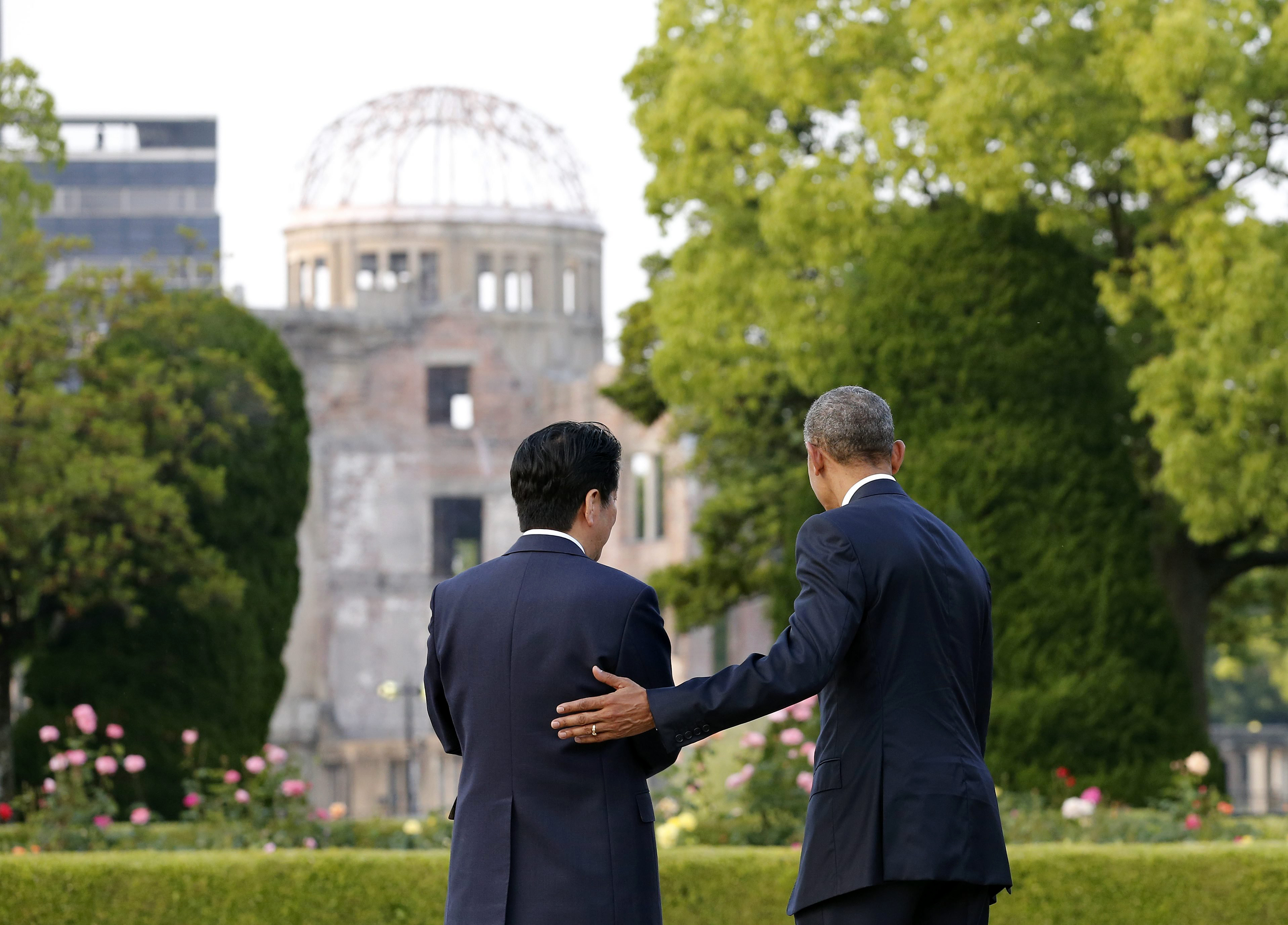 U.S. Presdent Barack Obama puts his hand on the back of Japanese Prime Minister Shinzo Abe at Hiroshima Peace Memorial Park, viewing the Atomic Bomb Dome in Hiroshima, western Japan, May 27, 2016.