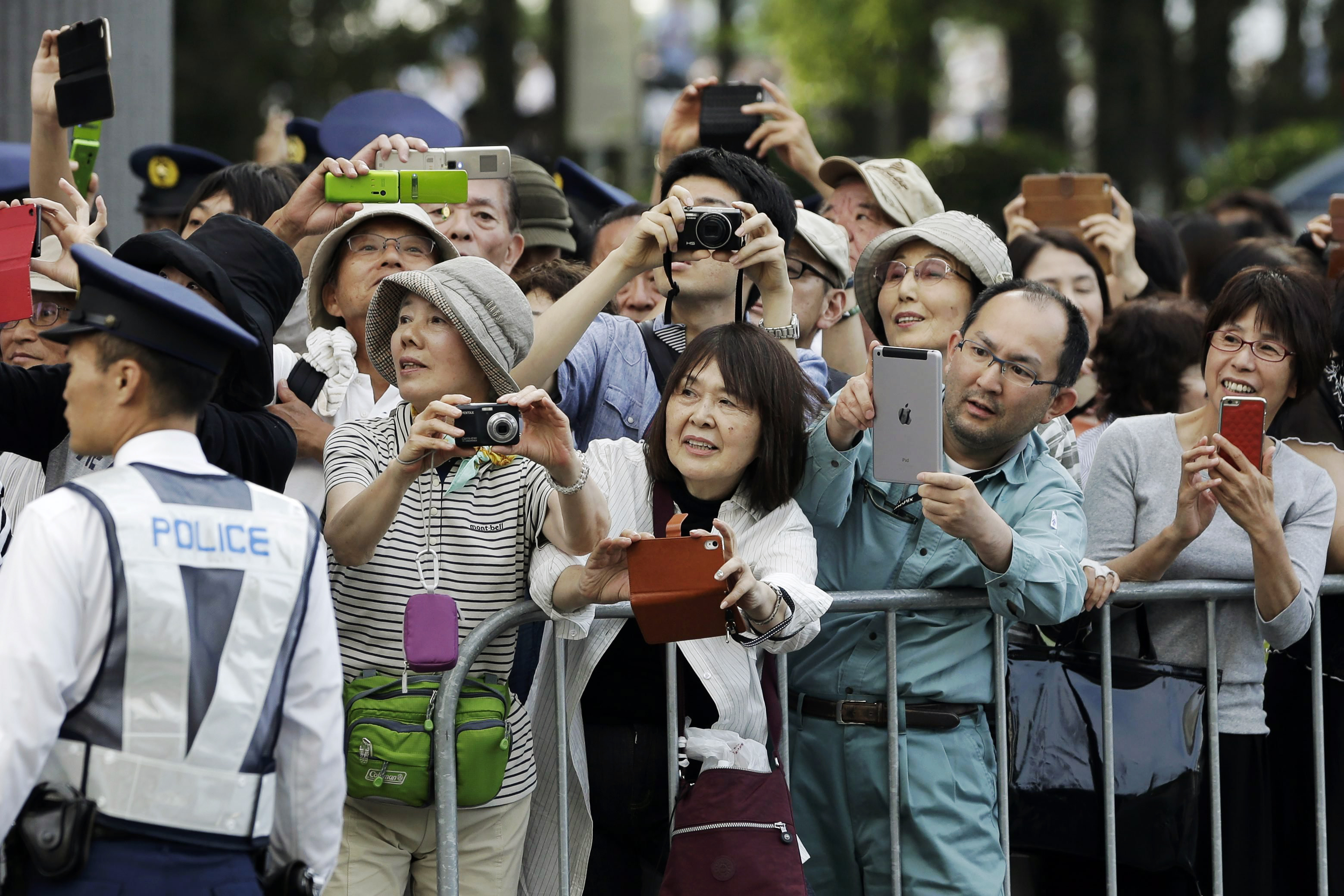 People gather to watch the arrival of President Barack Obama around Hiroshima Peace Memorial Park in Hiroshima, on May 27, 2016.
