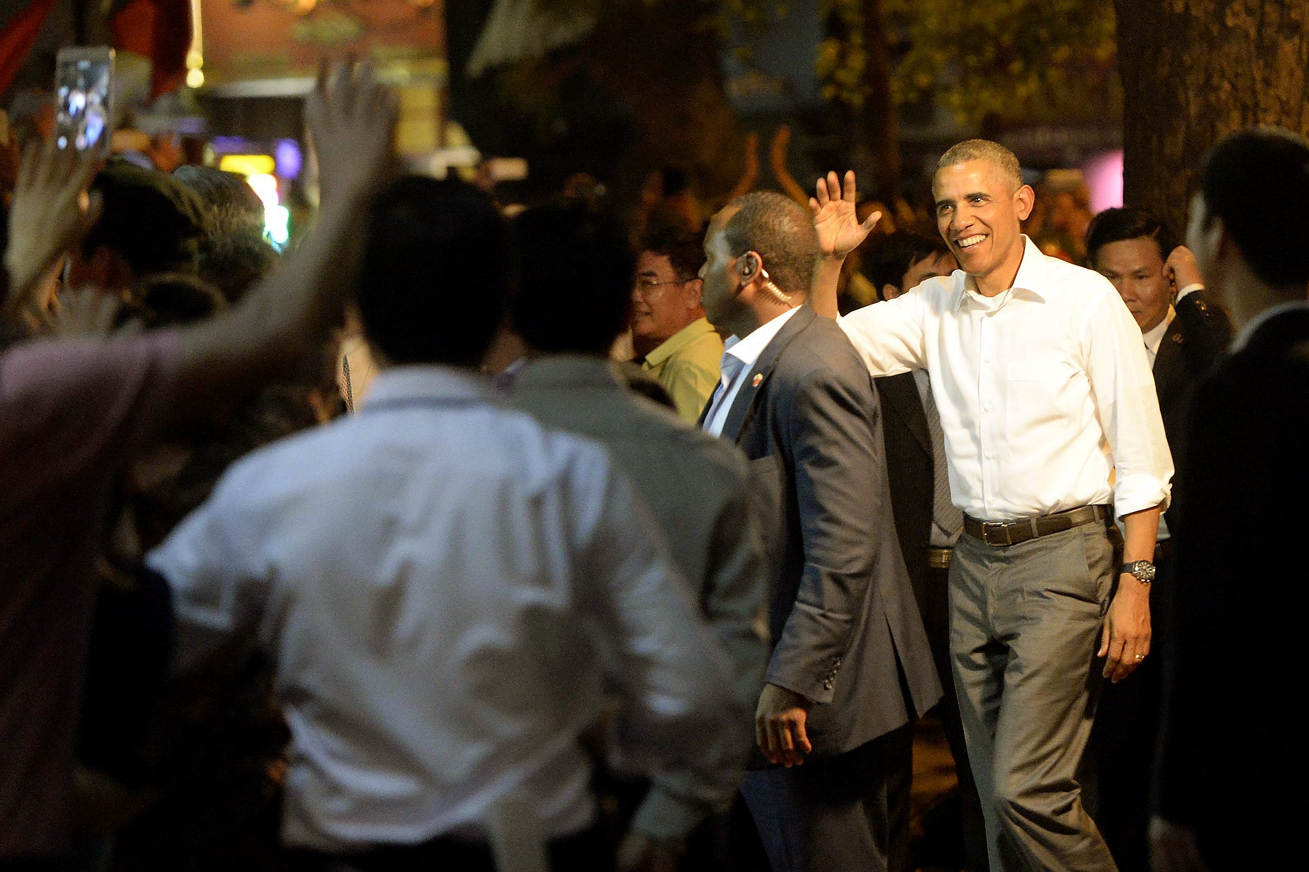 President Barack Obama  waves to local people as he enters a restaurant which serves bun cha, traditional Vietnamese dish of noodle and grilled pork, in Hanoi, Vietnam on May 23.
