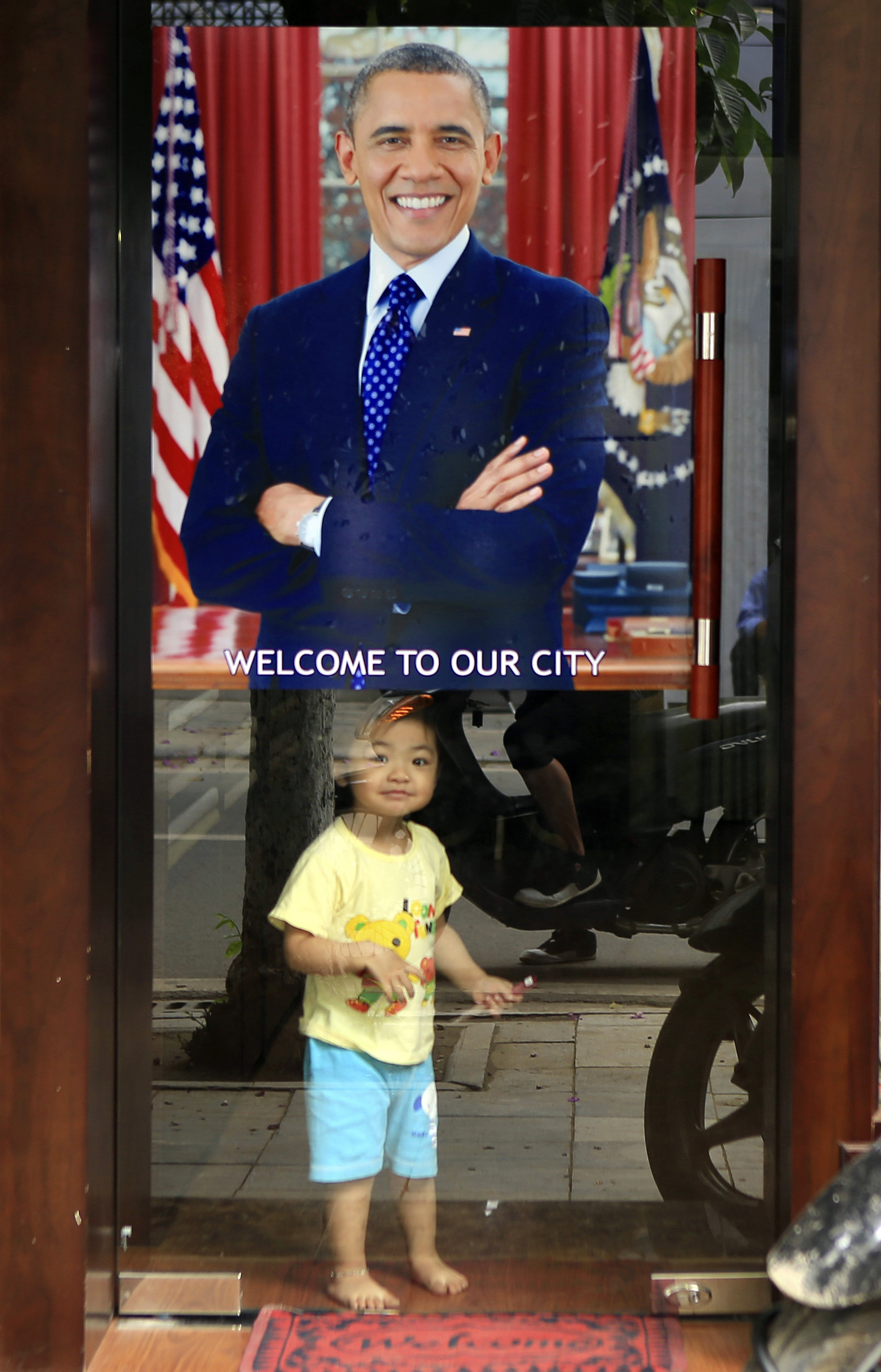 "A young girl looks out  under a poster of U.S President Barack Obama with a footnote reading ""Welcome to our city"", hung on the door of a shop in Hanoi, Vietnam on Sunday, May 22, 2016."