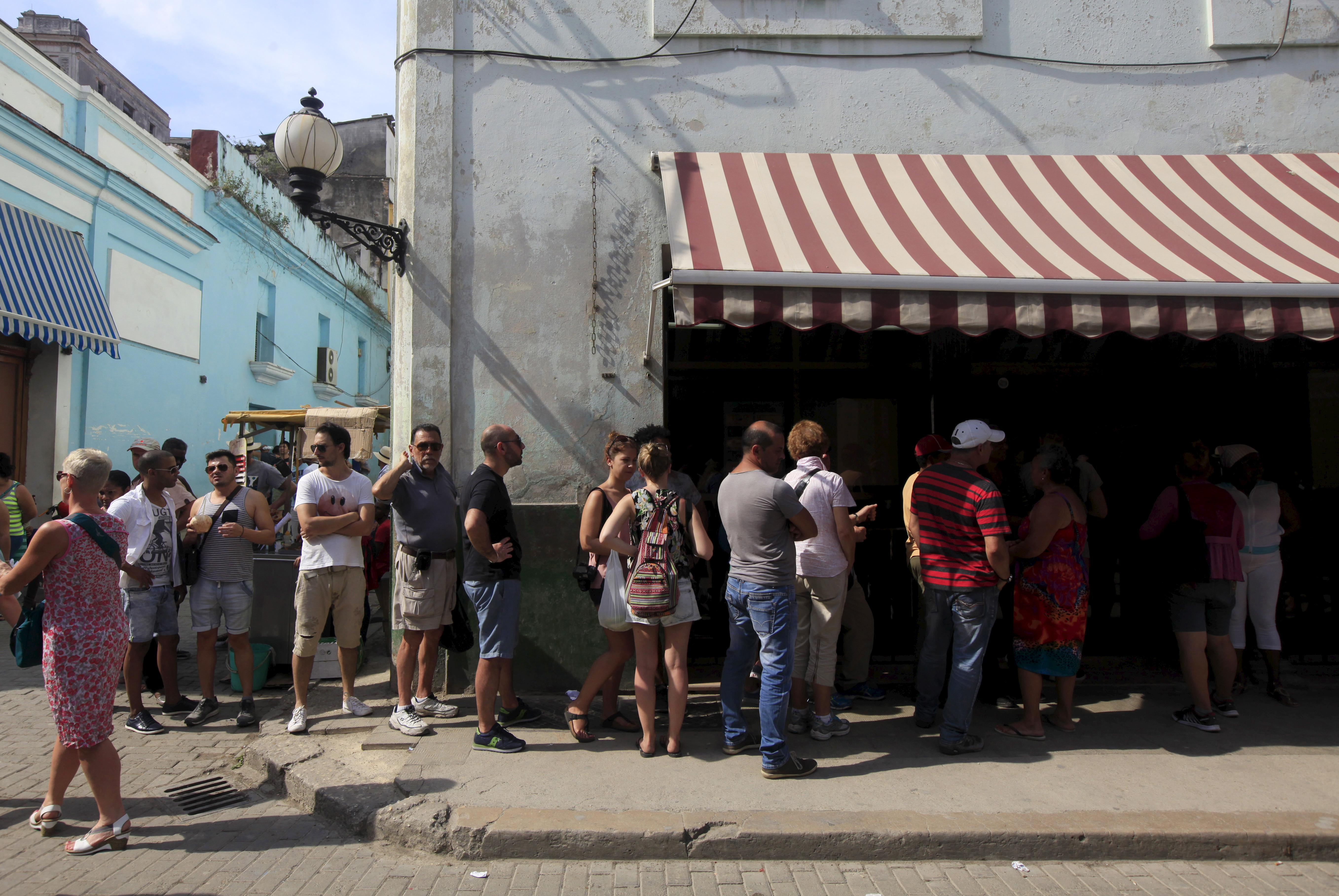 People stand outside a currency exchange shop to change money in Havana, March 17, 2016