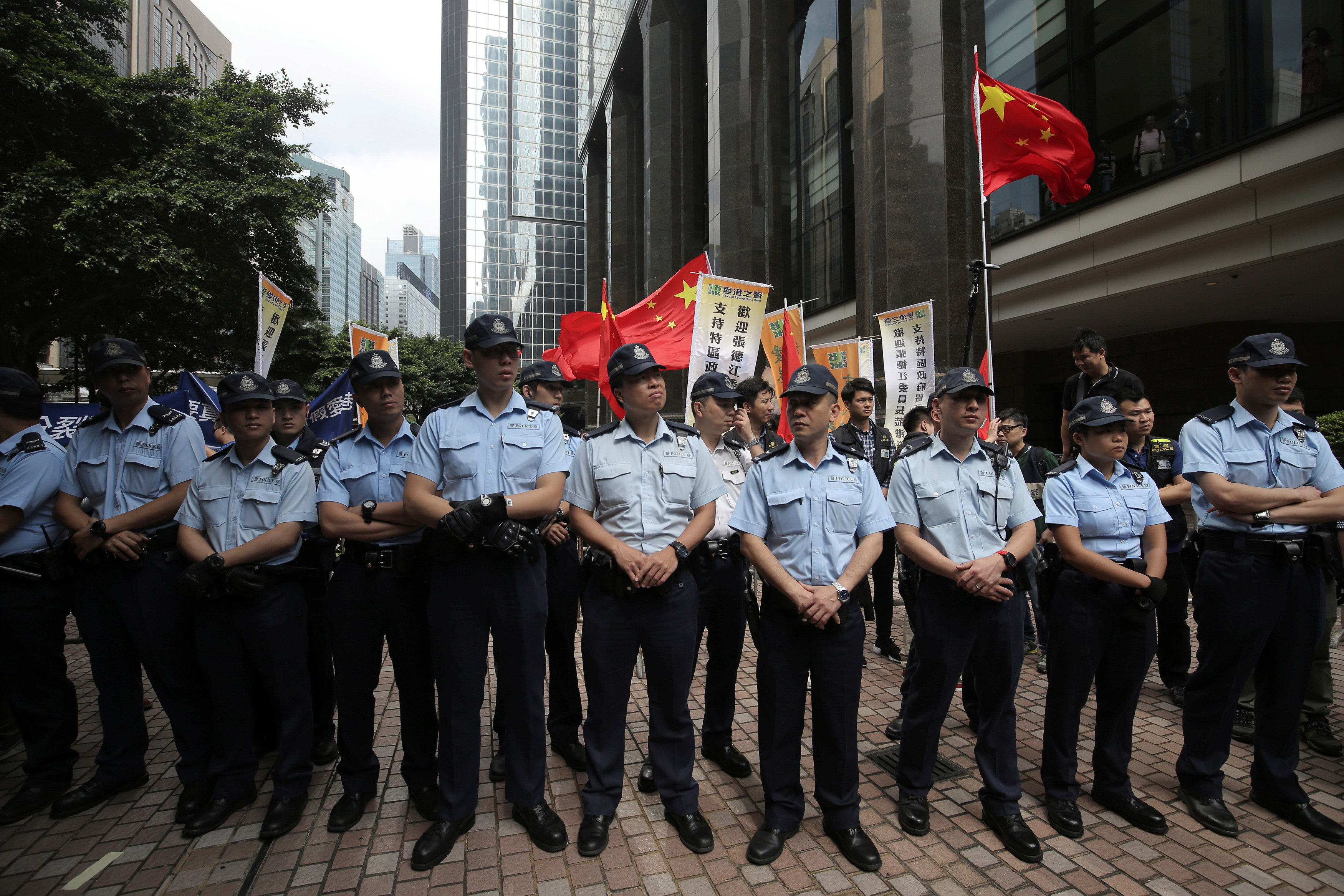 Police officers patrol in front of supporters of visiting Zhang Dejiang, the chairman of China's National People's Congress, during a protest against him in Hong Kong on May 18, 2016