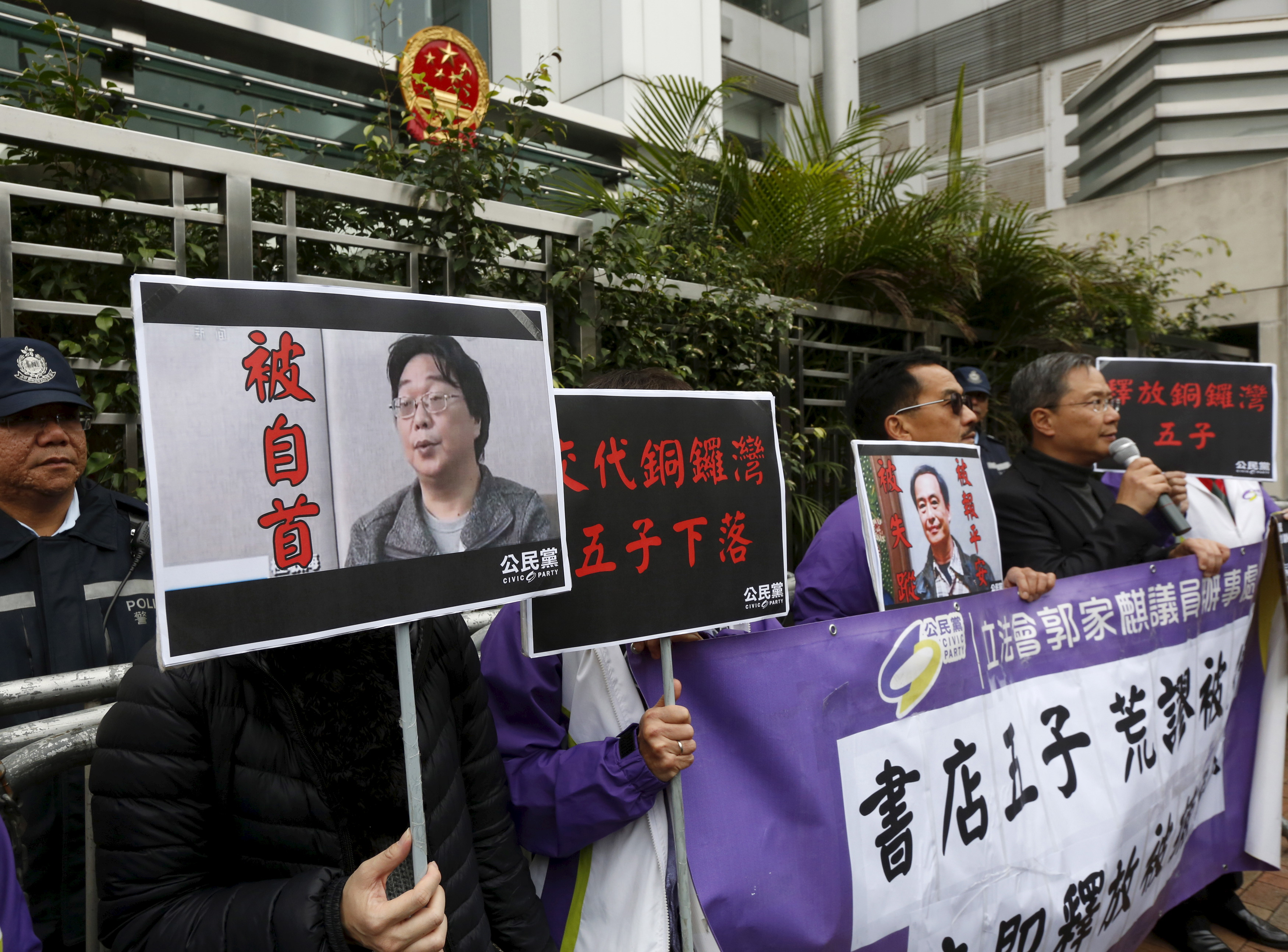 Members from the pro-democracy Civic Party carry a portrait of Gui Minhai (L) and Lee Bo during a protest outside the Chinese Liaison Office in Hong Kong, Jan. 19, 2016.