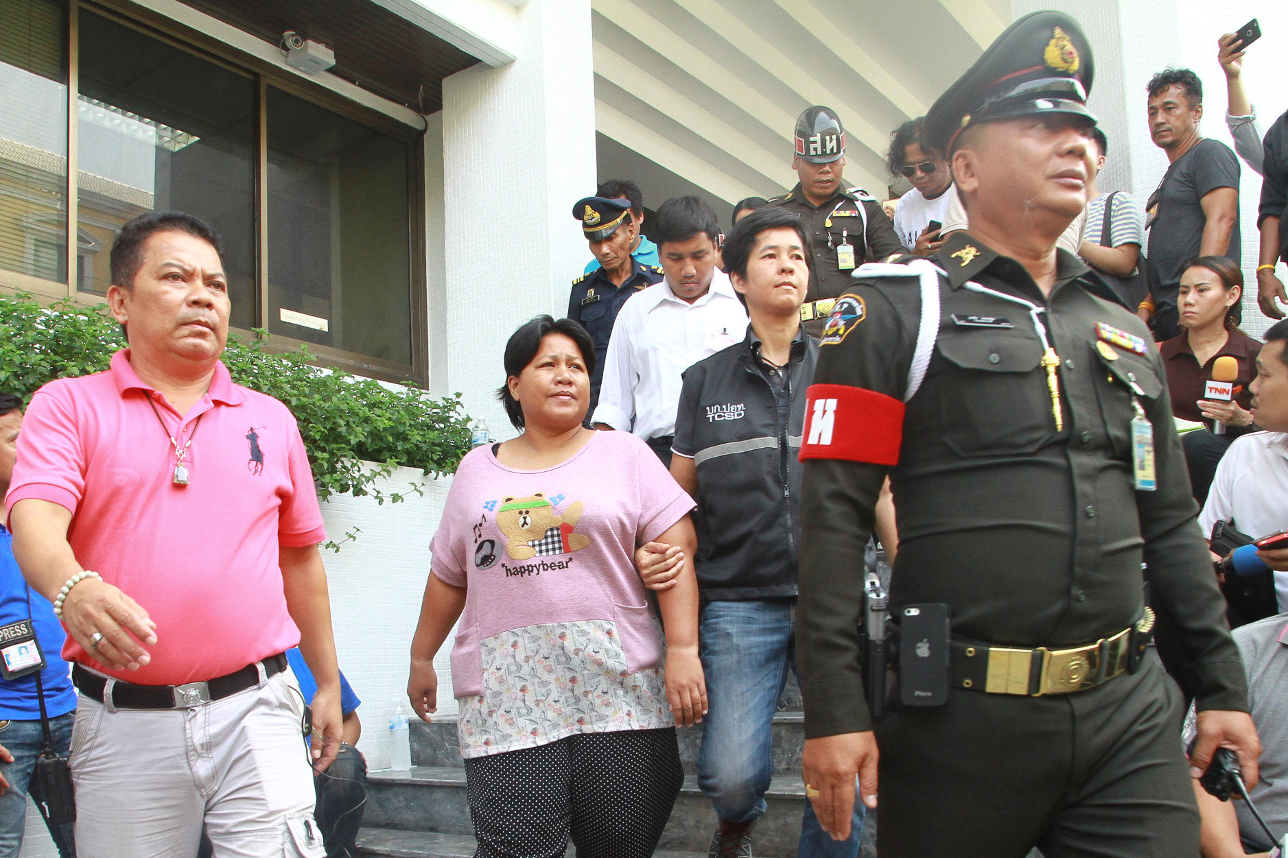 Patnaree Chankij (C), the mother of an anti-junta activist, is escorted by police as she leaves a military court in Bangkok, Thailand, May 8, 2016