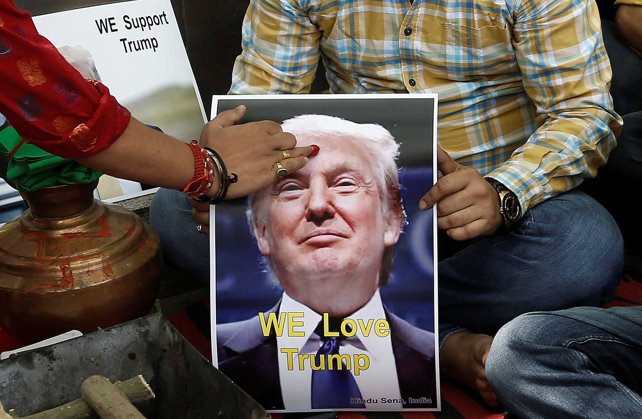 A priest applies a tika on the portrait of U.S. Republican presidential candidate Donald Trump during a special prayer organized by Hindu Sena, a right-wing group, in New Delhi on May 11, 2016
