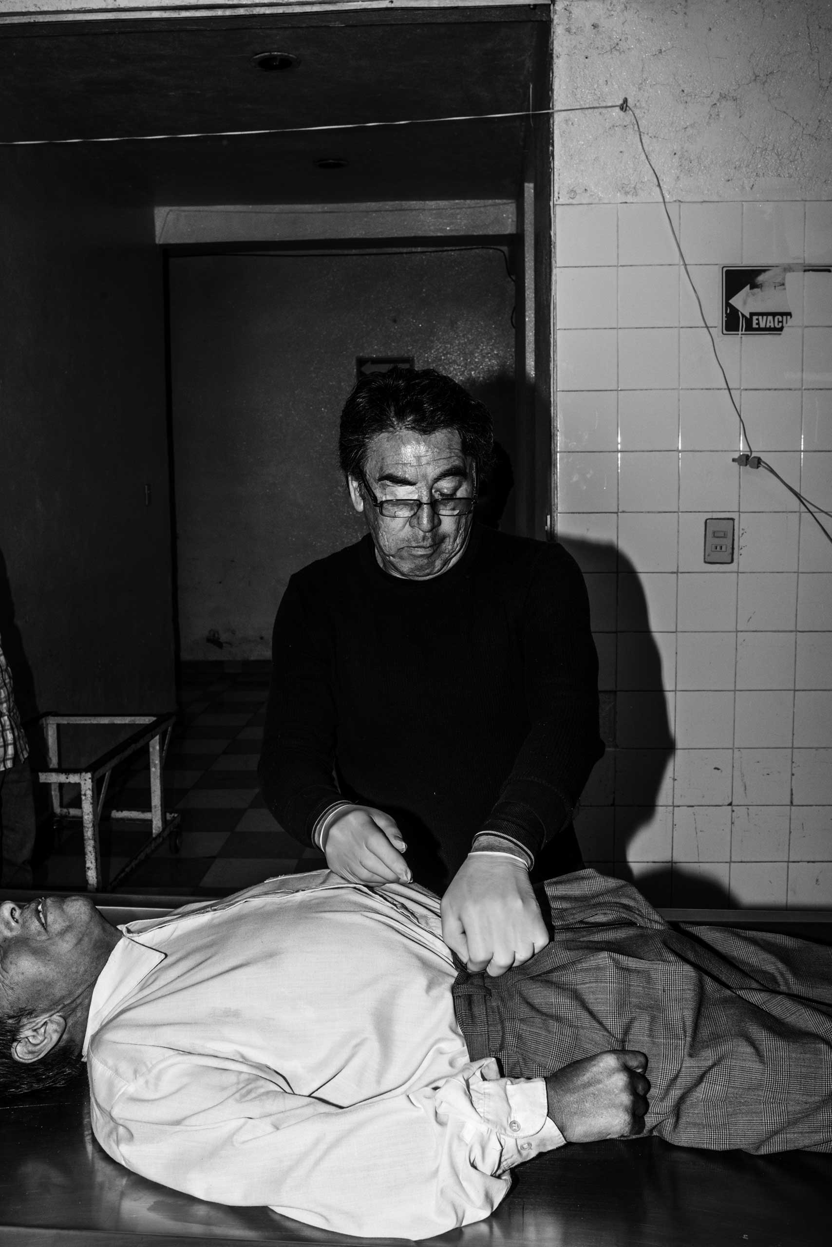 Arthuro, an employee of the Embalsamadores Funeral Office dresses up a body before putting it in a coffin. March 9, 2016.