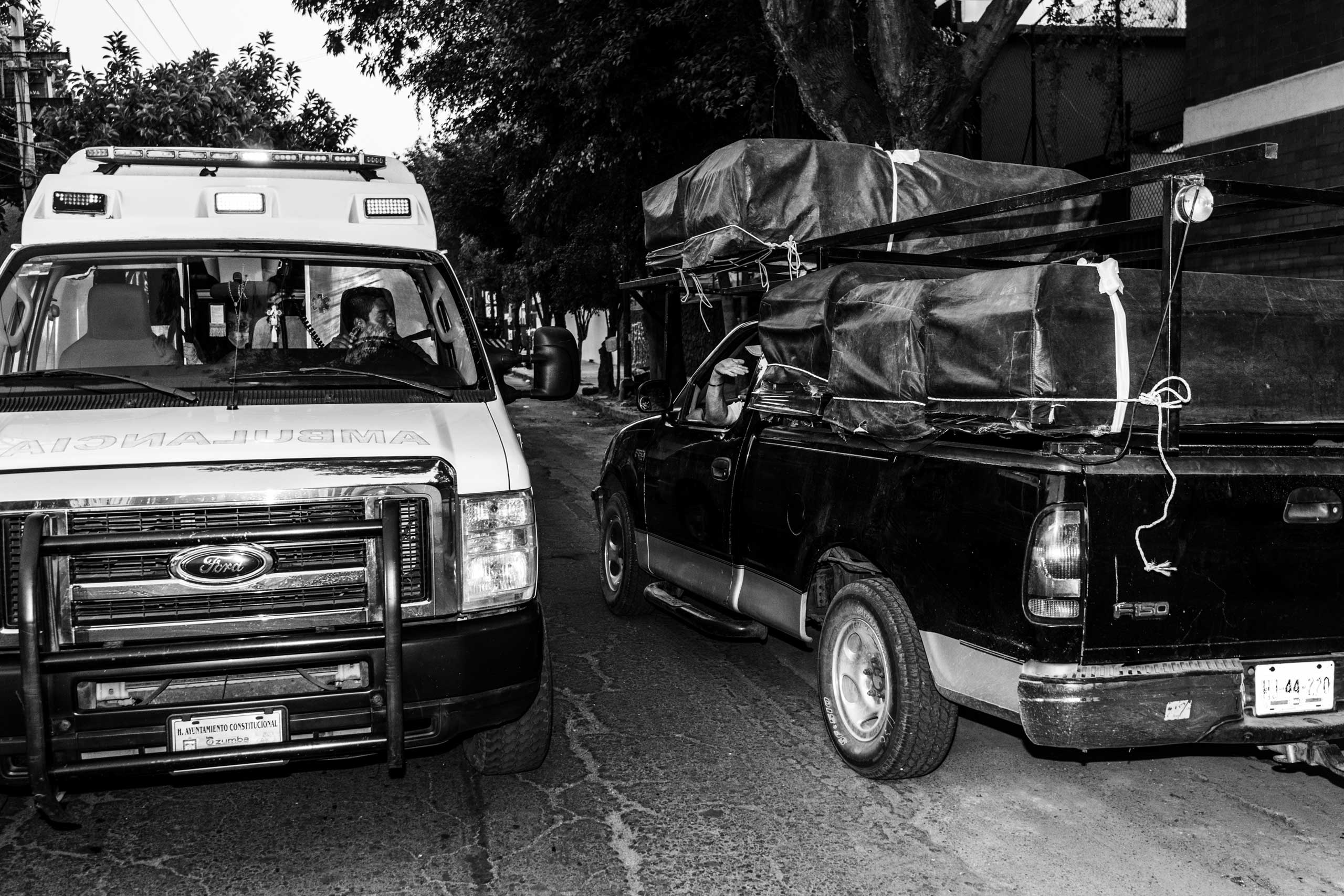 An itinerant seller of coffins talks to an ambulance driver, gathering information about funerals stores in need of coffins. March 13, 2016.