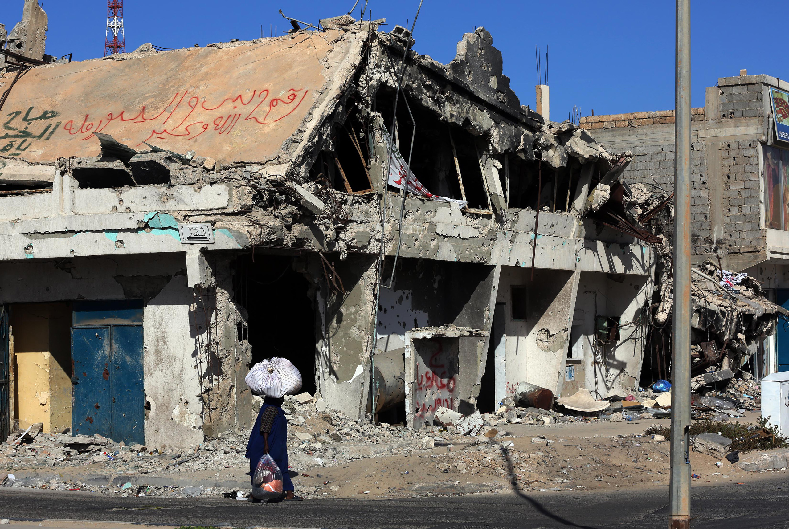 A Libyan woman walks past the rubble of a building in the Mediterranean city of Sirte, Oct. 13, 2012.