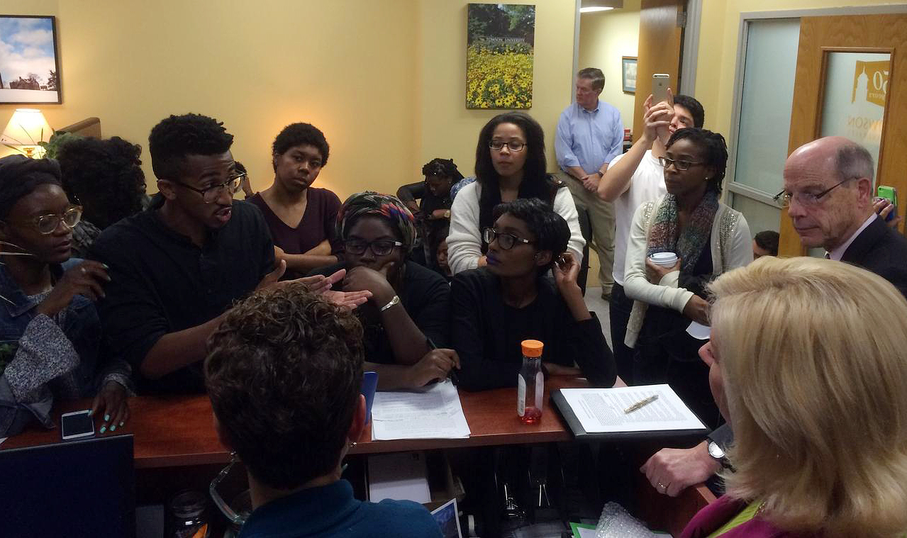 Student activists, including Bilphena Yahwon, left, and John Gillespie, second left, talk with administrators, including then-Interim President Timothy Chandler, right, at a student-led sit-in of the president's office at Towson University on Nov. 18, 2015.