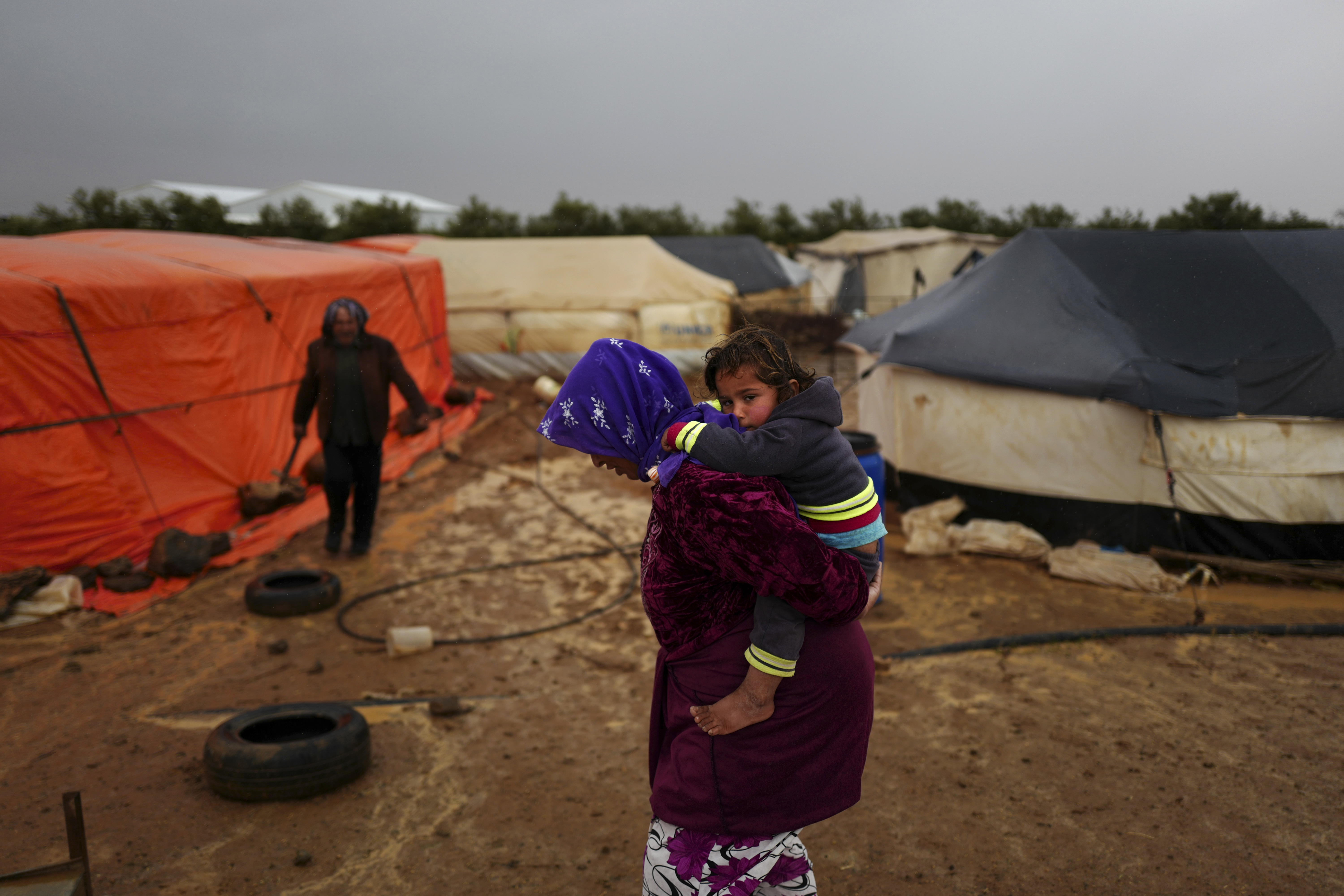 A Syrian refugee carries her child as she heads back to her tent through muddy grounds during a rainfall at an informal tented settlement near the Syrian border, on the outskirts of Mafraq, Jordan, March 28, 2016.