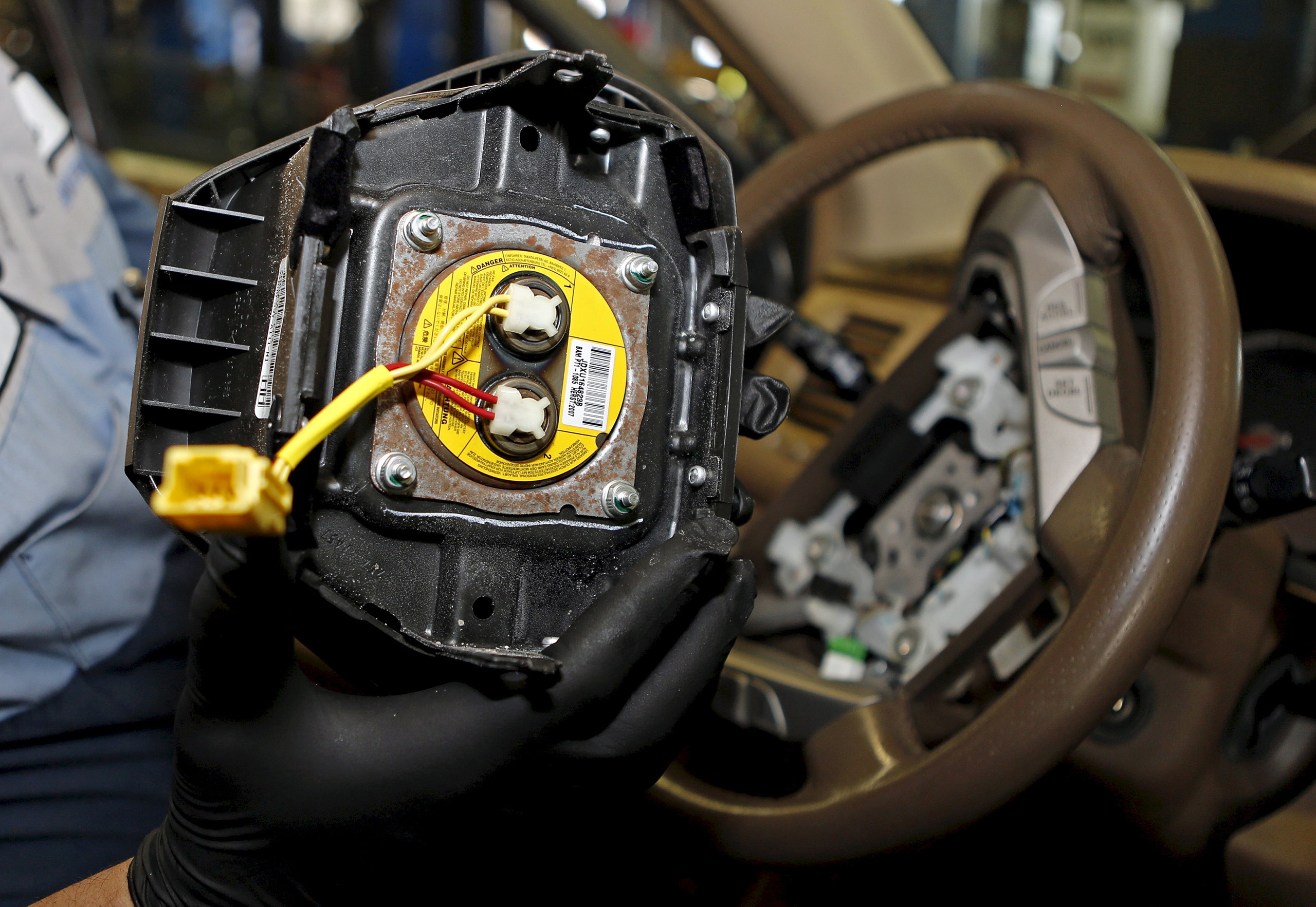A technician holds a recalled Takata airbag inflator in Miami, Florida June 25, 2015.