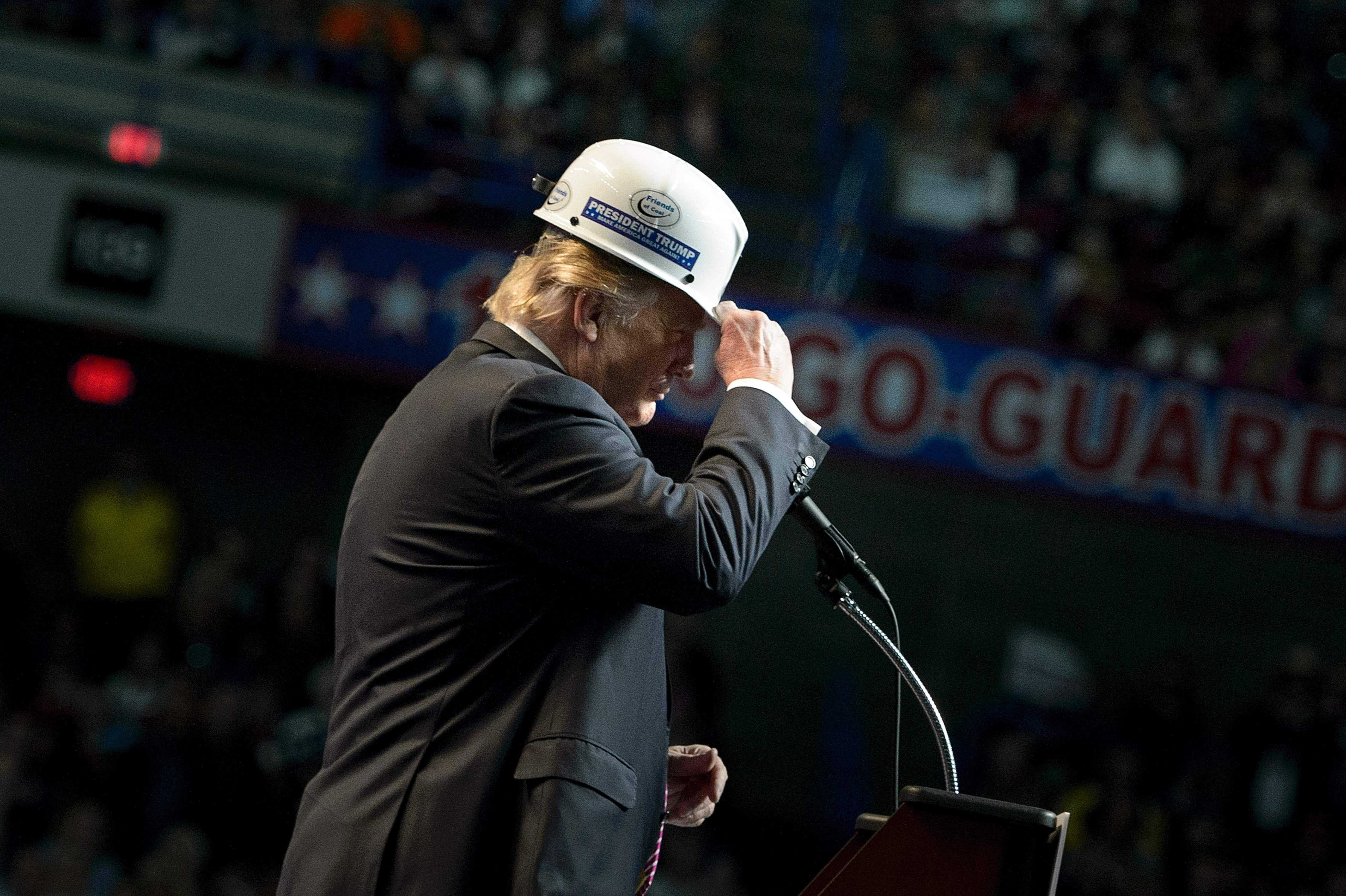 Donald Trump puts on a miner's hat while speaking during a rally on May 5, 2016 in Charleston, West Virginia.