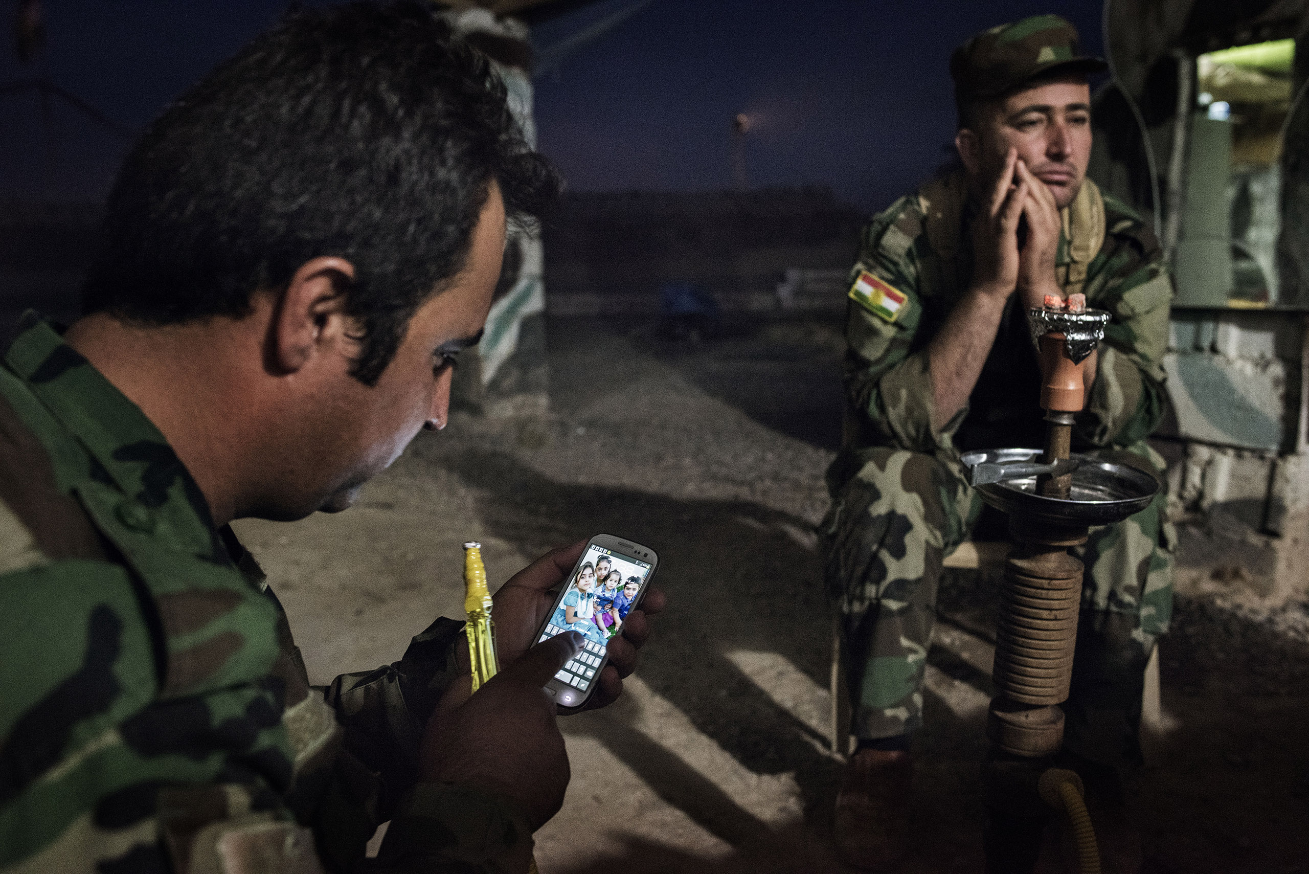 Sgt. Farsal Goran looks at his cellphone as he sits with Majid Hamid, 32, while shisha is smoked at the front outside Makhmour, Iraq, May 8, 2016.