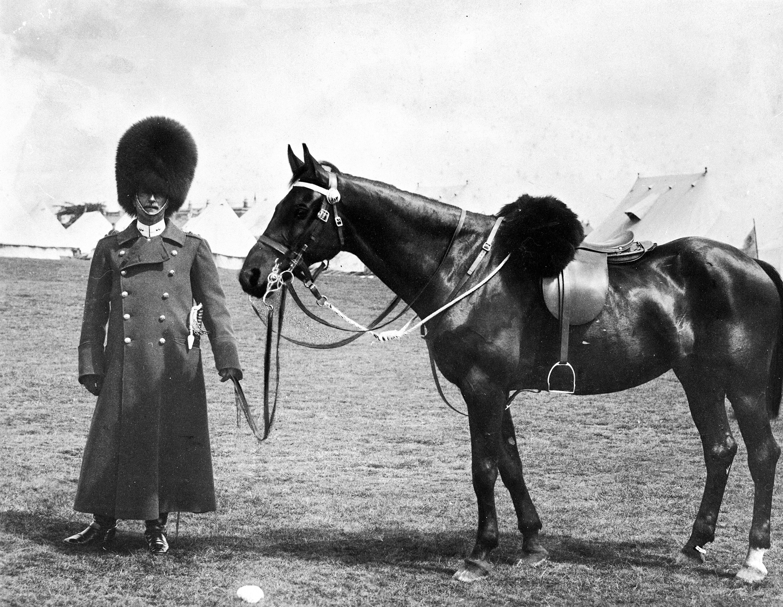 A Grenadier Guard wearing the grenadier's bearskin cap at a military encampment in Dublin, circa 1910.