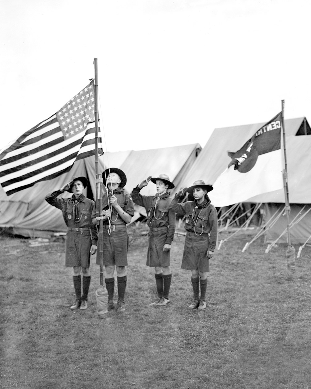 American boy scouts from New York, hauling up the American flag in front of their camp at Arrowe Park, Birkenhead in readiness for the International Scout Jamboree. United Kingdom, 1929.