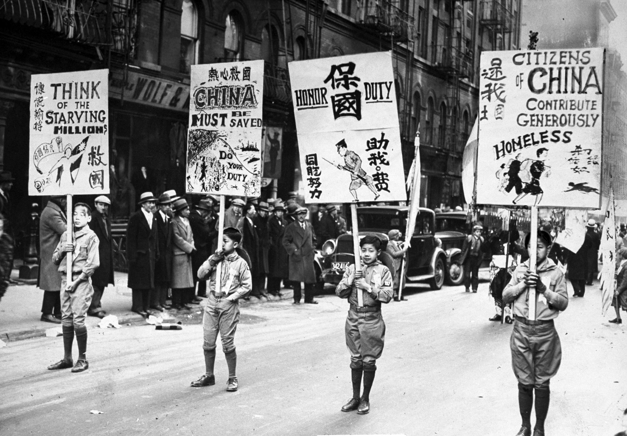 Boy Scouts carry banners in parade through Chinatown seeking aid for China's homeless.