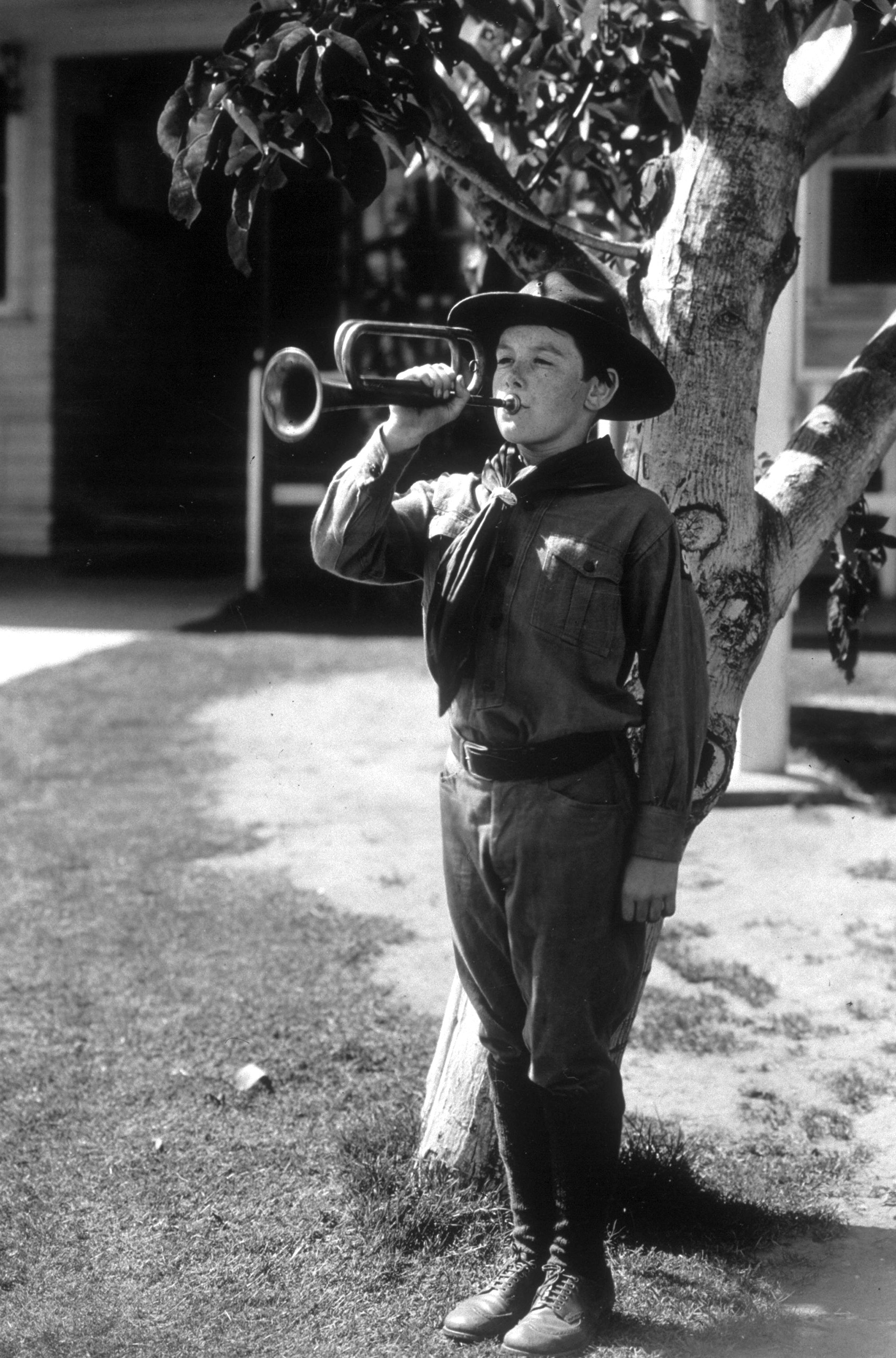 Child actor Junior Coghlan playing the trumpet in a scout uniform. Circa 1935.