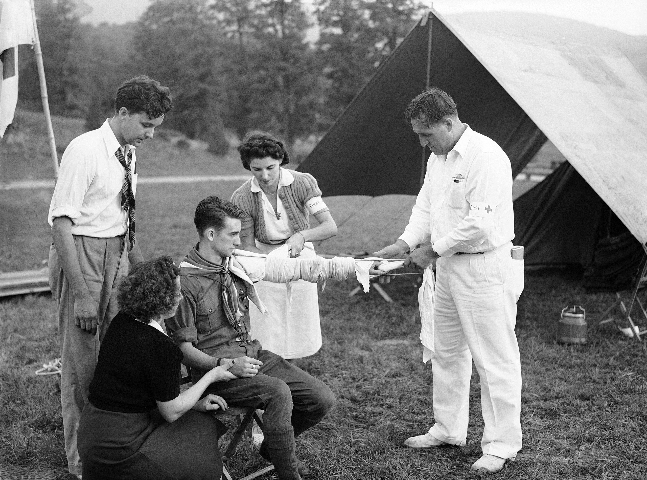 A Boy Scout has his arm tied up in a splint after it has been dressed by Red Cross workers from Poughkeepsie, N.Y., following the  evacuation  of about 2,000 New Yorkers who left for Dutchess County in New York, Sept. 9, 1941. Simulating wartime conditions volunteers left the city and drove north to avoid an imaginary  bombing  of New York. It was part of a demonstration of civilian defense work.