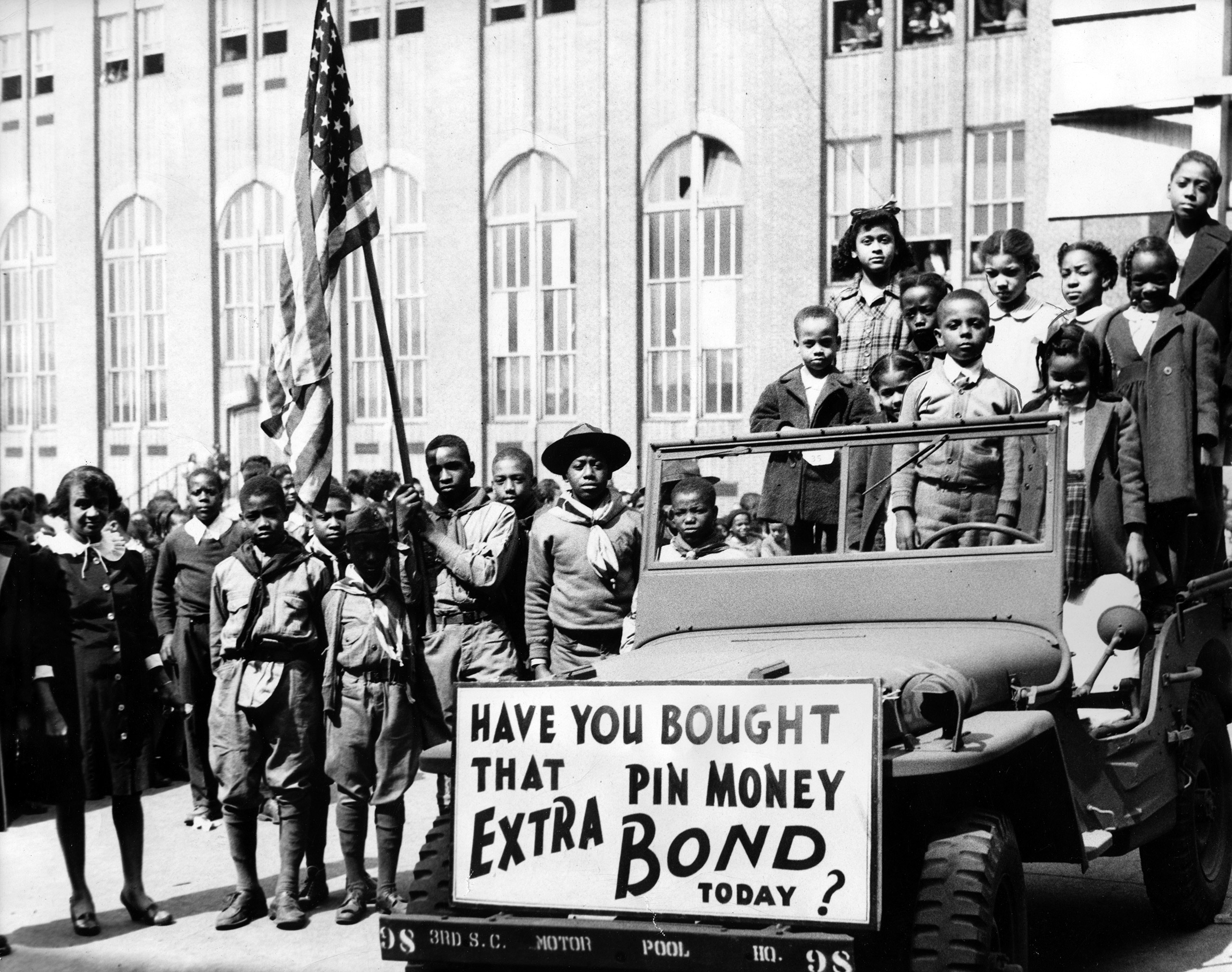 A group of boy scouts carrying the American flag and other children standing in and around a car with a board reading 'Have you bought that pin money extra bond today?, March 24, 1945.