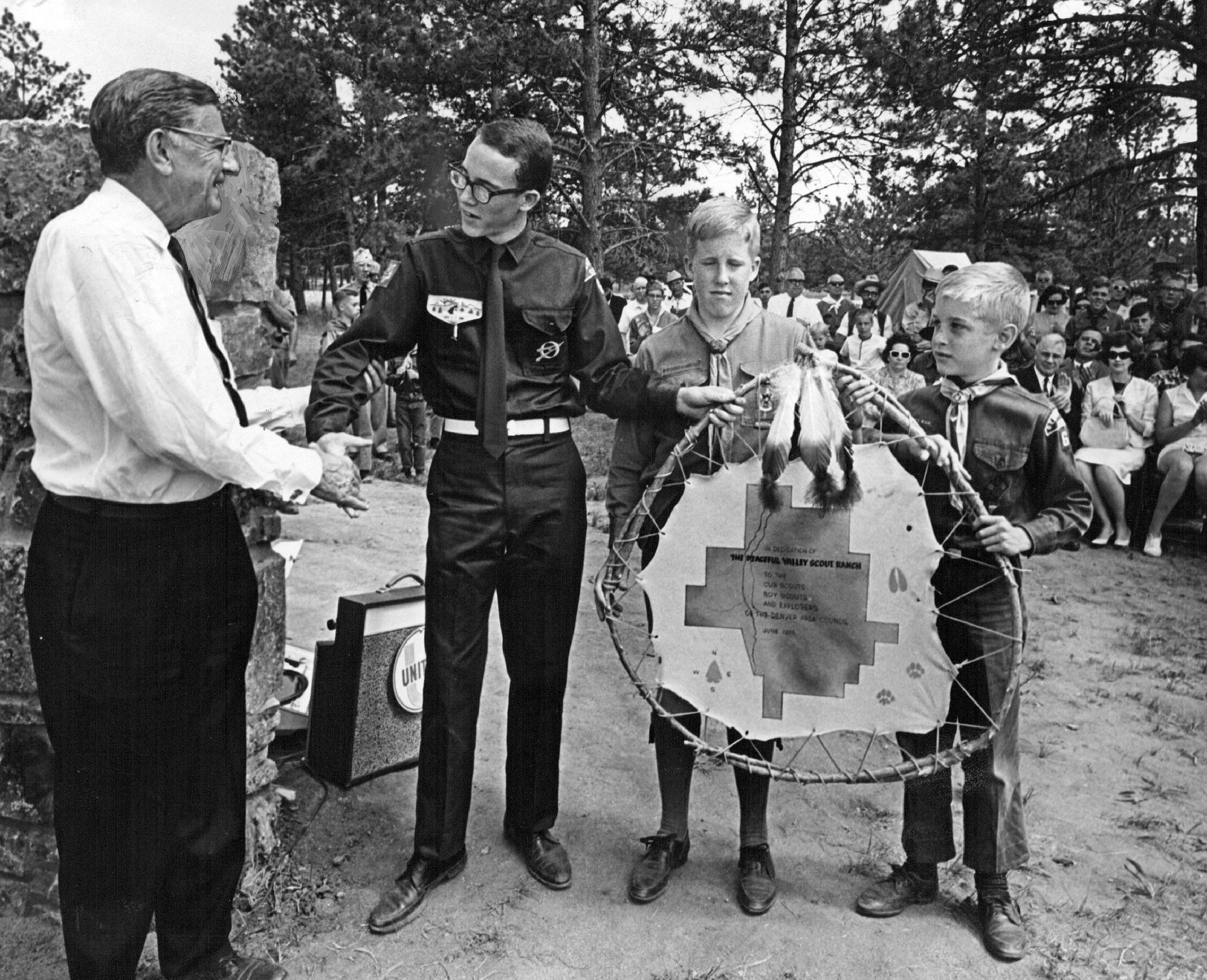 J. Clinton Bowman, president of the Denver Area Council, Boy Scouts of America, presents a leather map of the Peaceful Valley Scout Ranch to three representatives of the Scouts- from left, Keat, Phil and Roger Johnson. 1966.