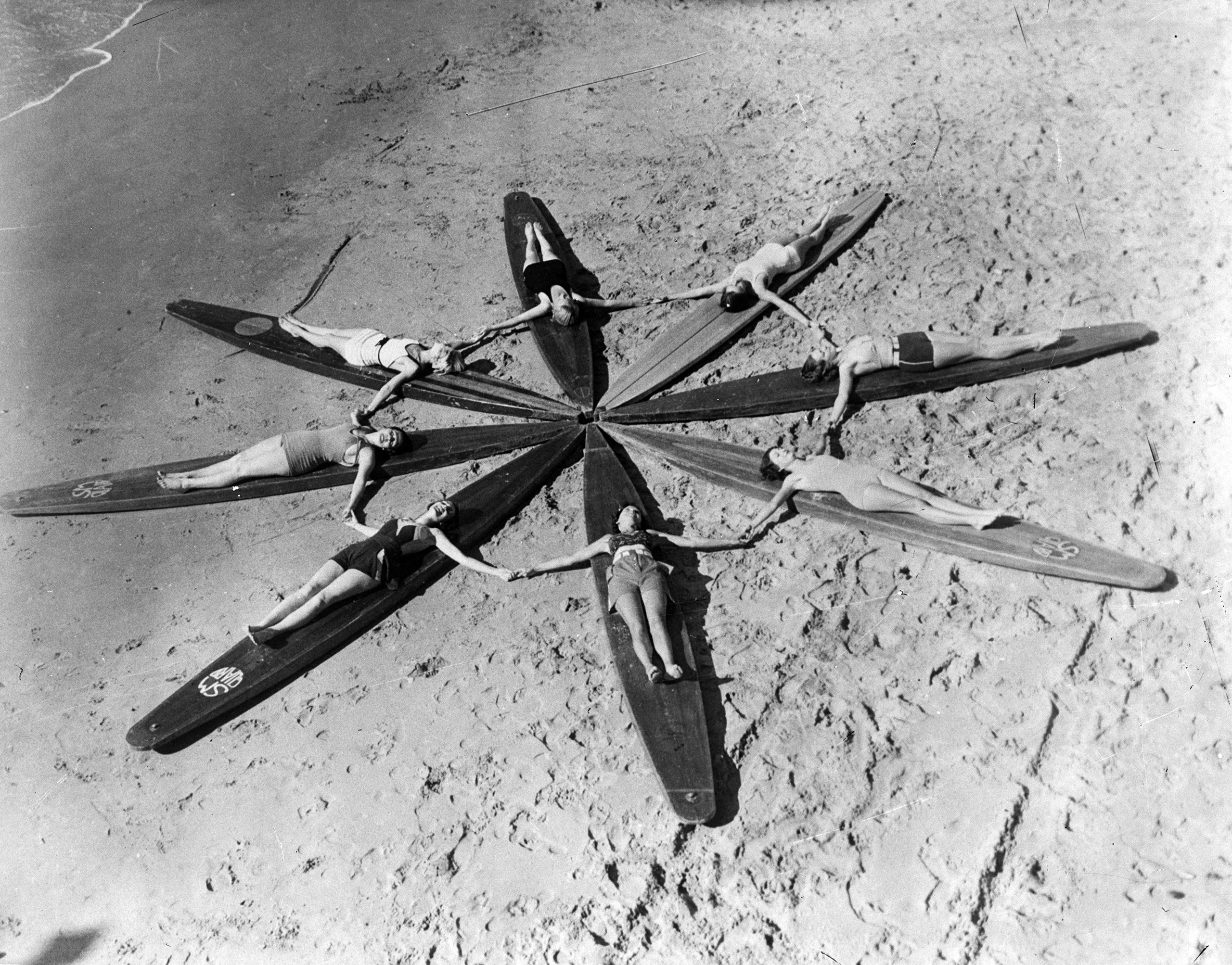 Women surfboarders form a star as they  lie on their huge hollow surfboards on Santa Monica beach, circa 1935.