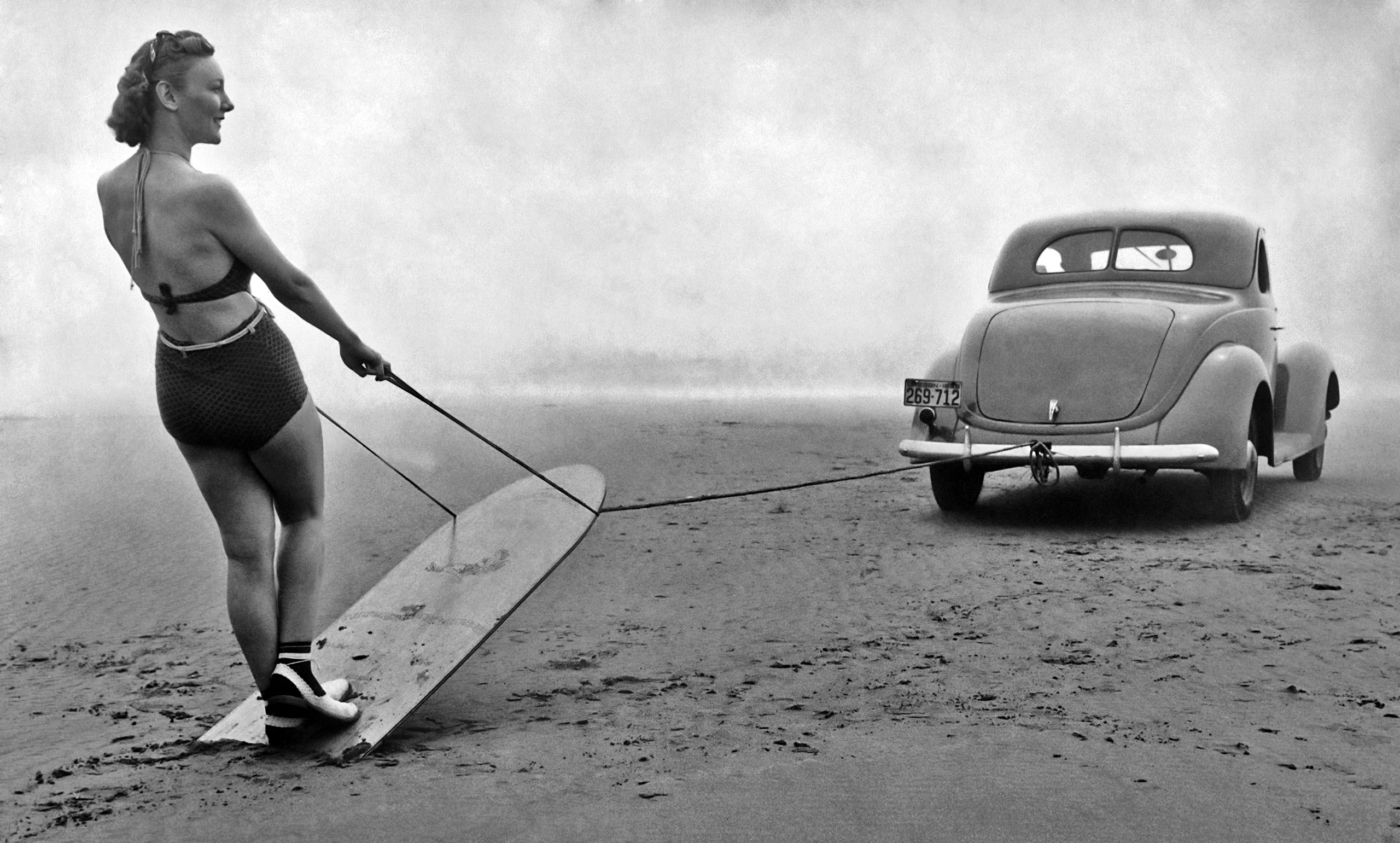 Geraldine Mathis being pulled along on her surfboard by a car driven along the sand near the mouth of the Necanicum River in Oregon circa 1940.
