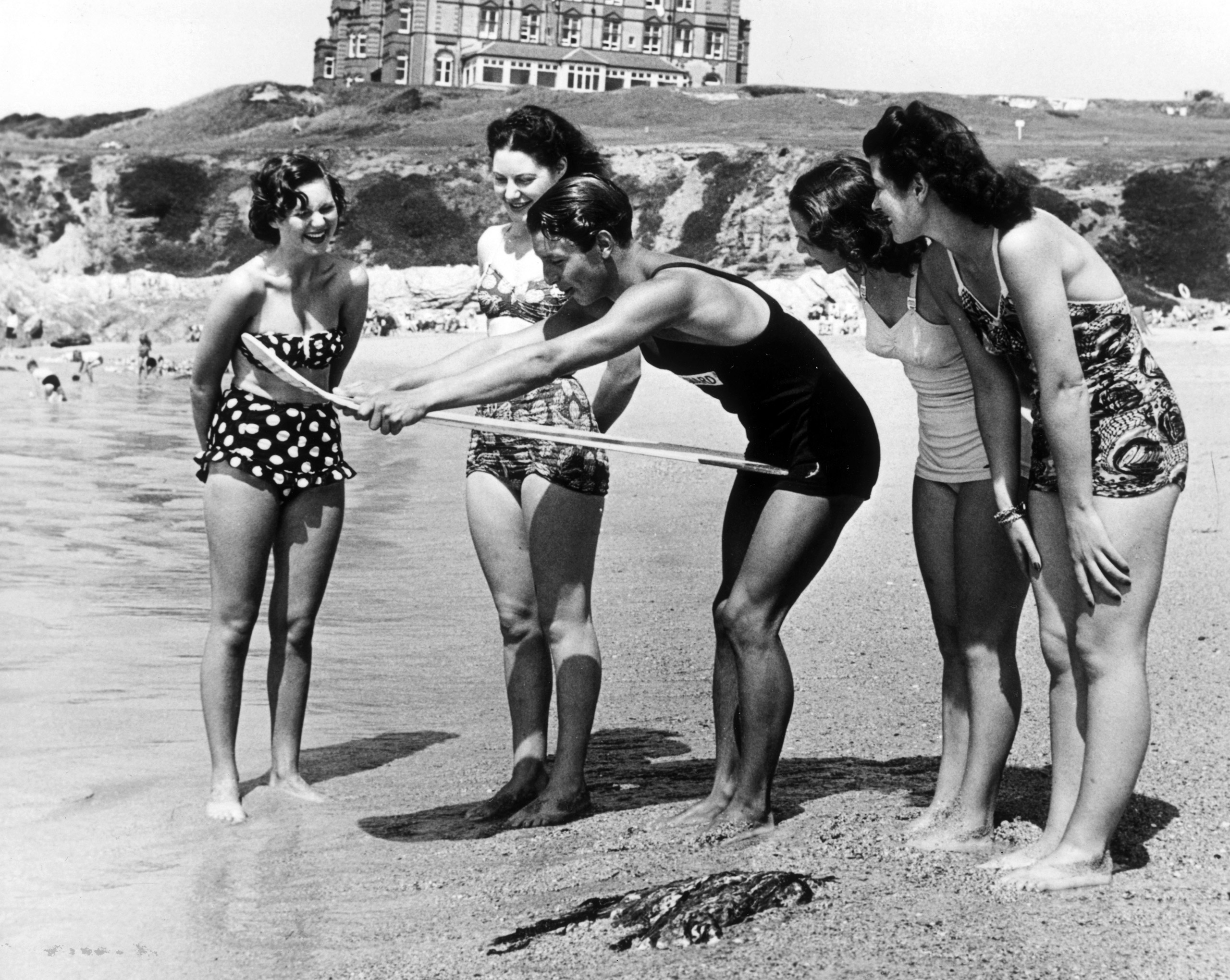 A lifeguard teaches four women how to handle a surfboard on the beach at Newquay in Cornwall, 1950.