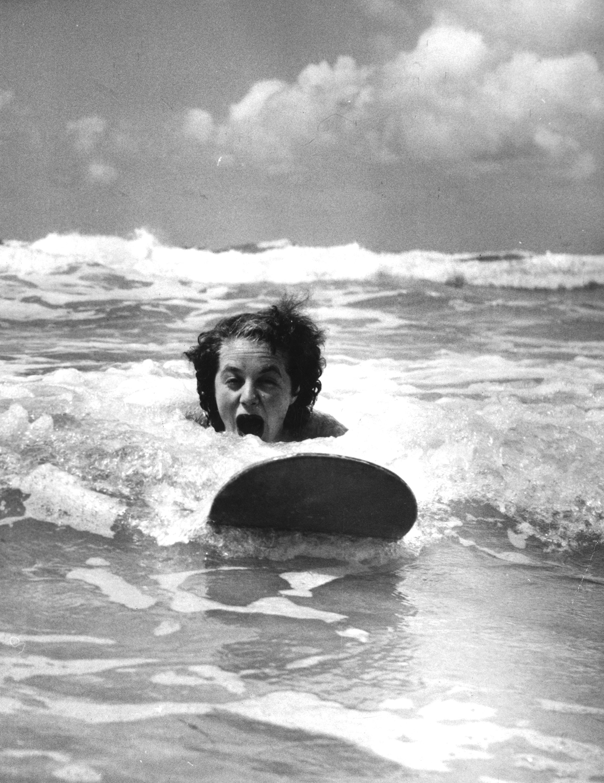 Expert surfer Betty Hunt riding the waves at Newquay, Cornwall, 1952.