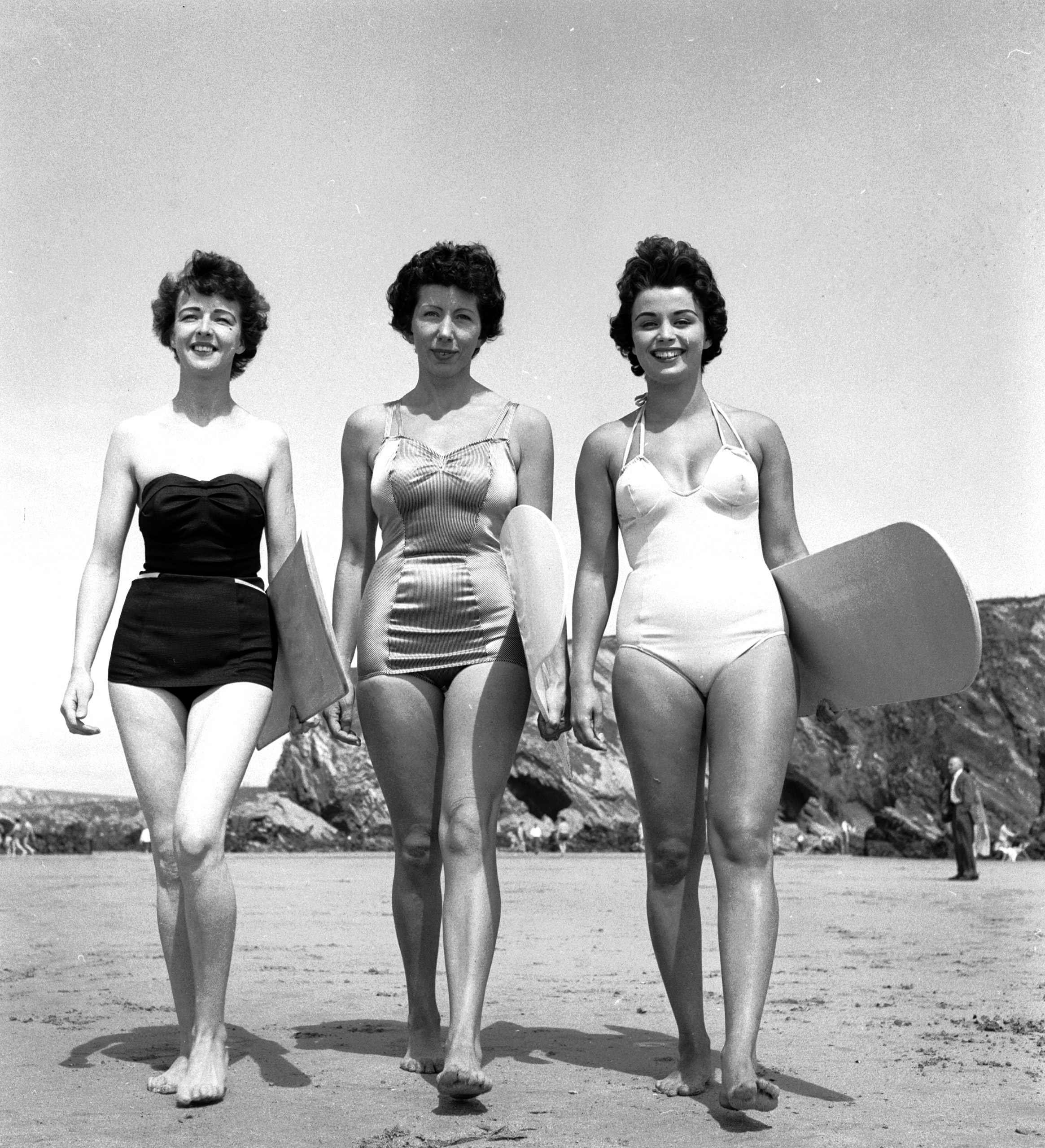 Three surfing girls (left to right, Marilyn Ridge, Lyn Connelly, Dee Delaney) prepare to ride the swell and maybe catch a tube or two down on Newquay beach, Cornwall, 1955.