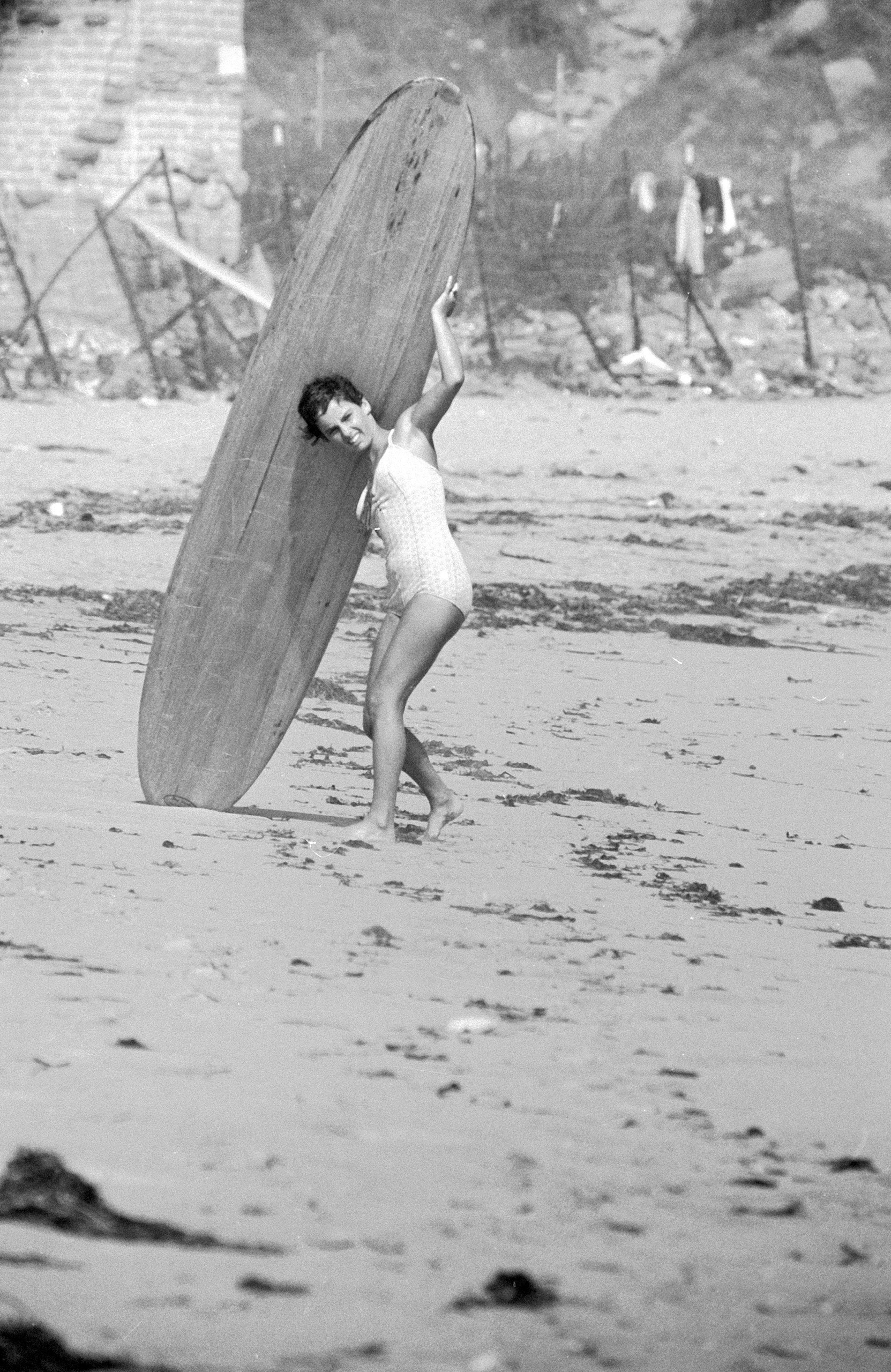 16 yr. old surfer Kathy (Gidget) Kohner on the beach with her surfboard, 1957.