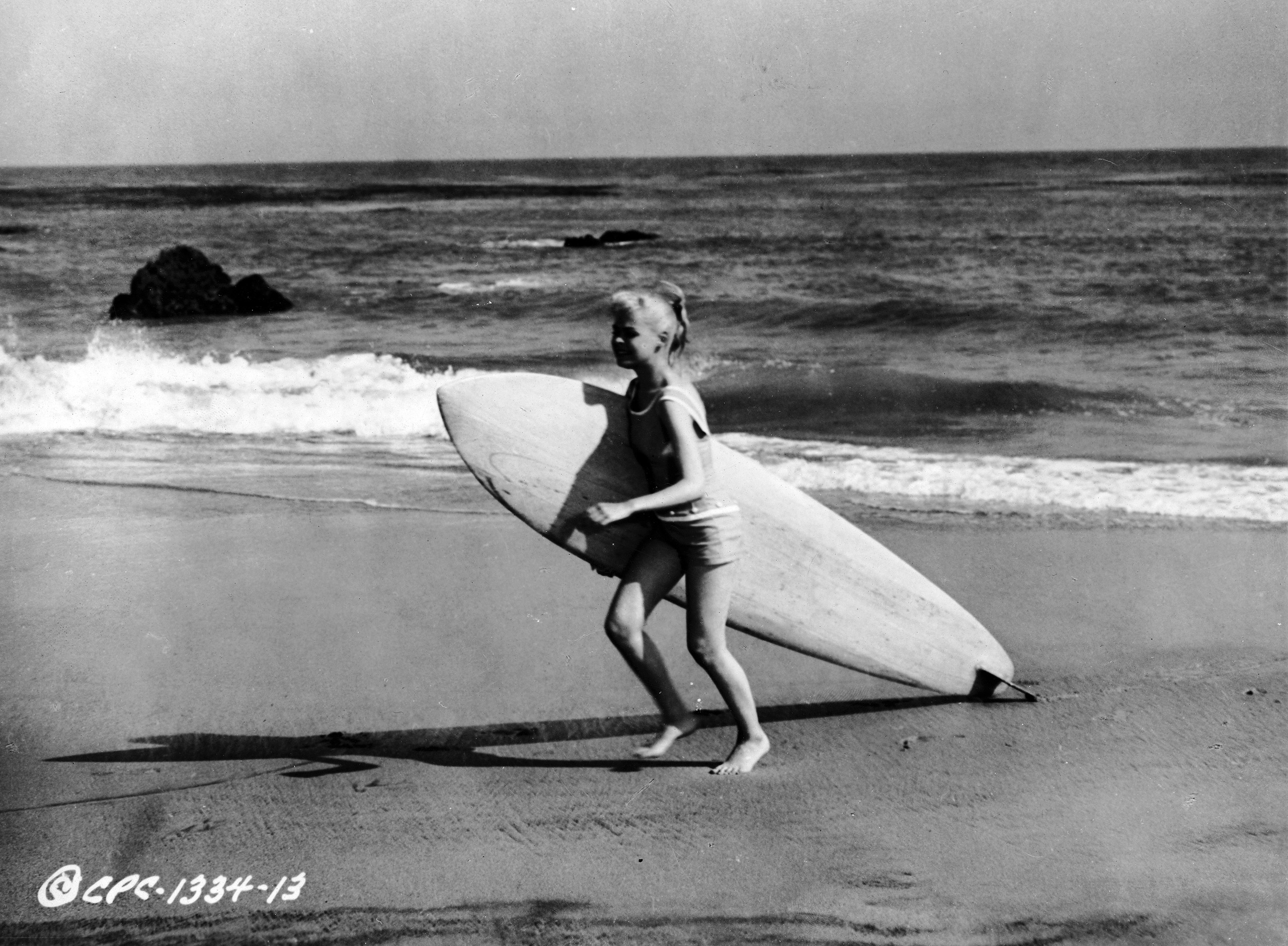 American actor Sandra Dee walks on the beach, carrying a surfboard in a still from the film, 'Gidget,' directed by Paul Wendkos, 1959.