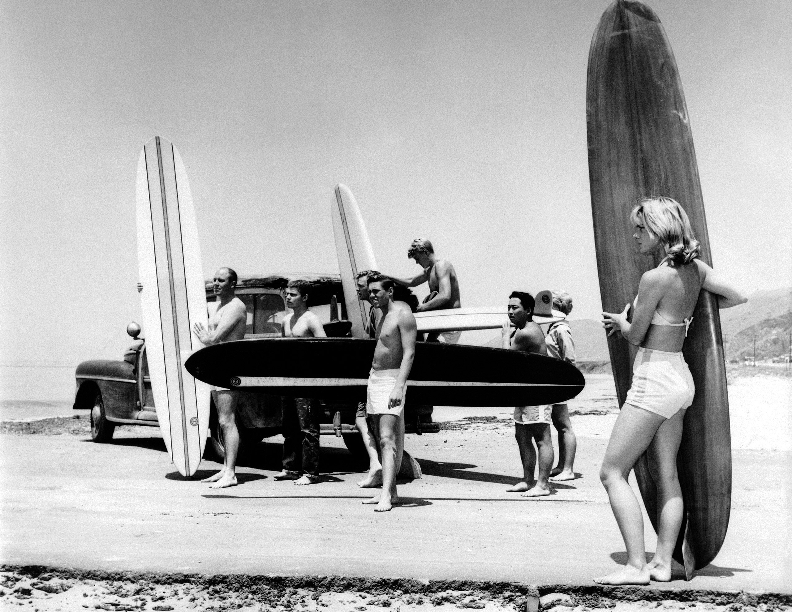 Members of the North Bay surfing club upload their surf boards from a station wagon at Malibu Beach, Calif. on July 12, 1961.