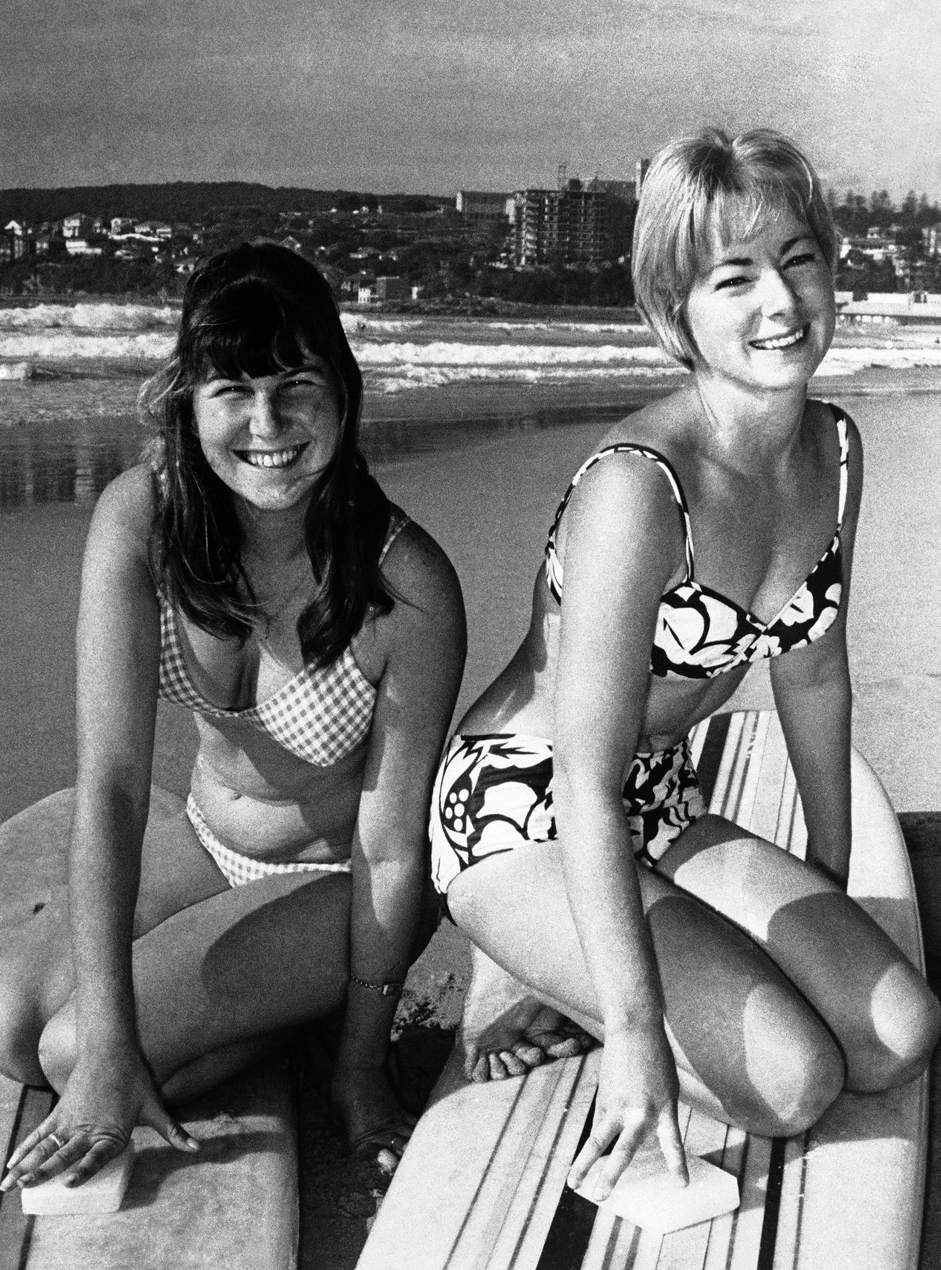 Maureen Horsley, 18, of Sydney, Australia, left, and American champion Linda Benson, 20, of the Encinitas Club of California, prepare for a dip in the Australian surf on May 16, 1964, in a warm-up for the World Surfboard Riding Championships at Sydney's Manly Beach.