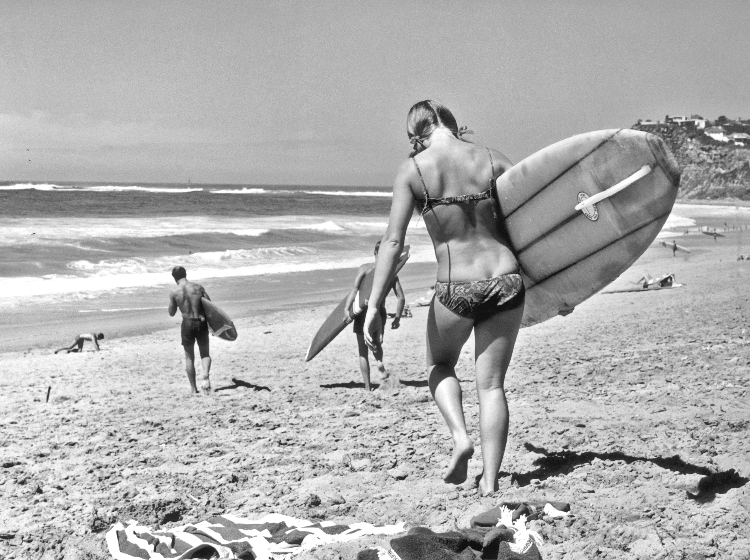 A woman carries her surf board down to the water on a beach near Sydney, Australia, circa 1965.
