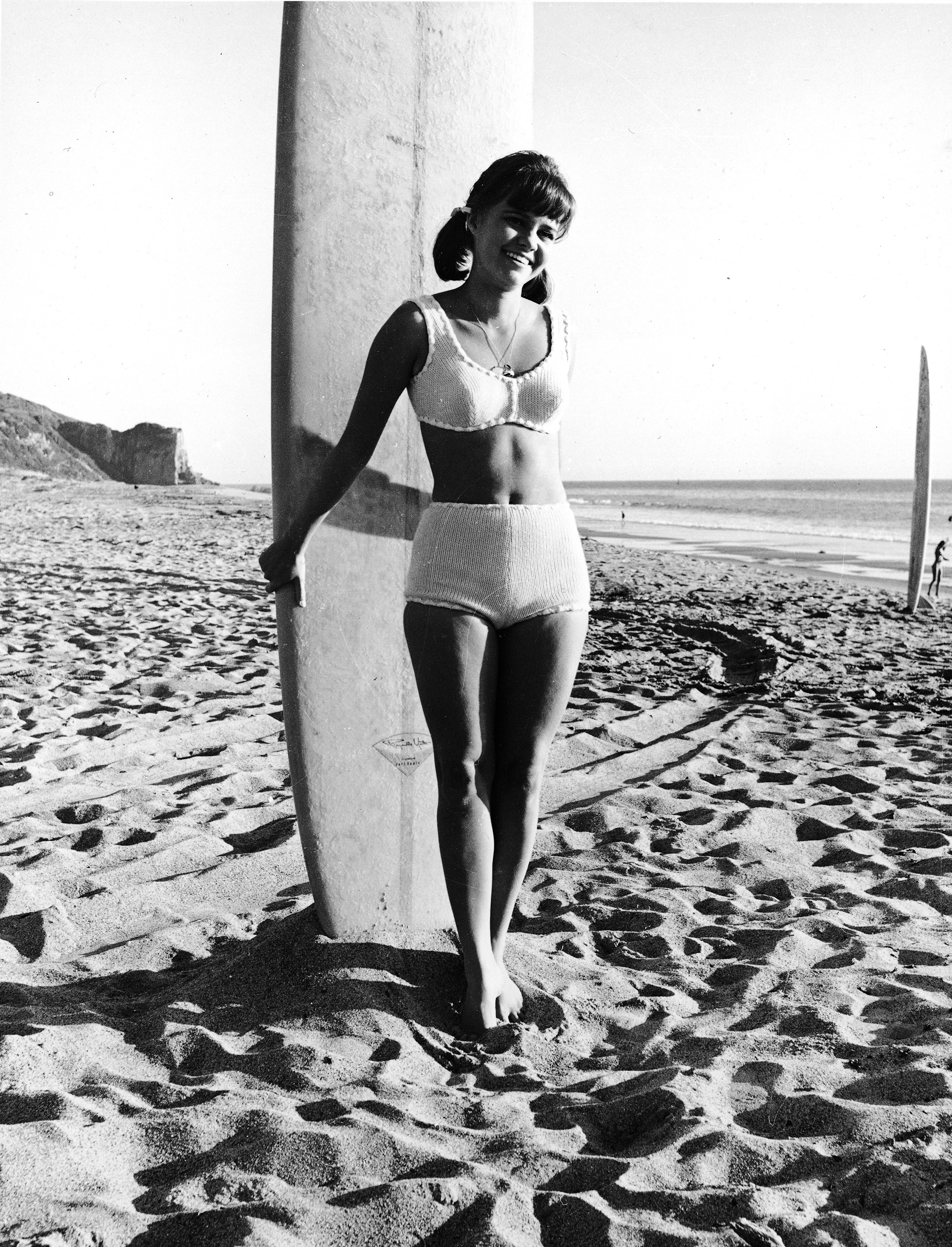 Sally Field from the television series, 'Gidget,' posing in a swimsuit with a surfboard on the beach, circa 1965.